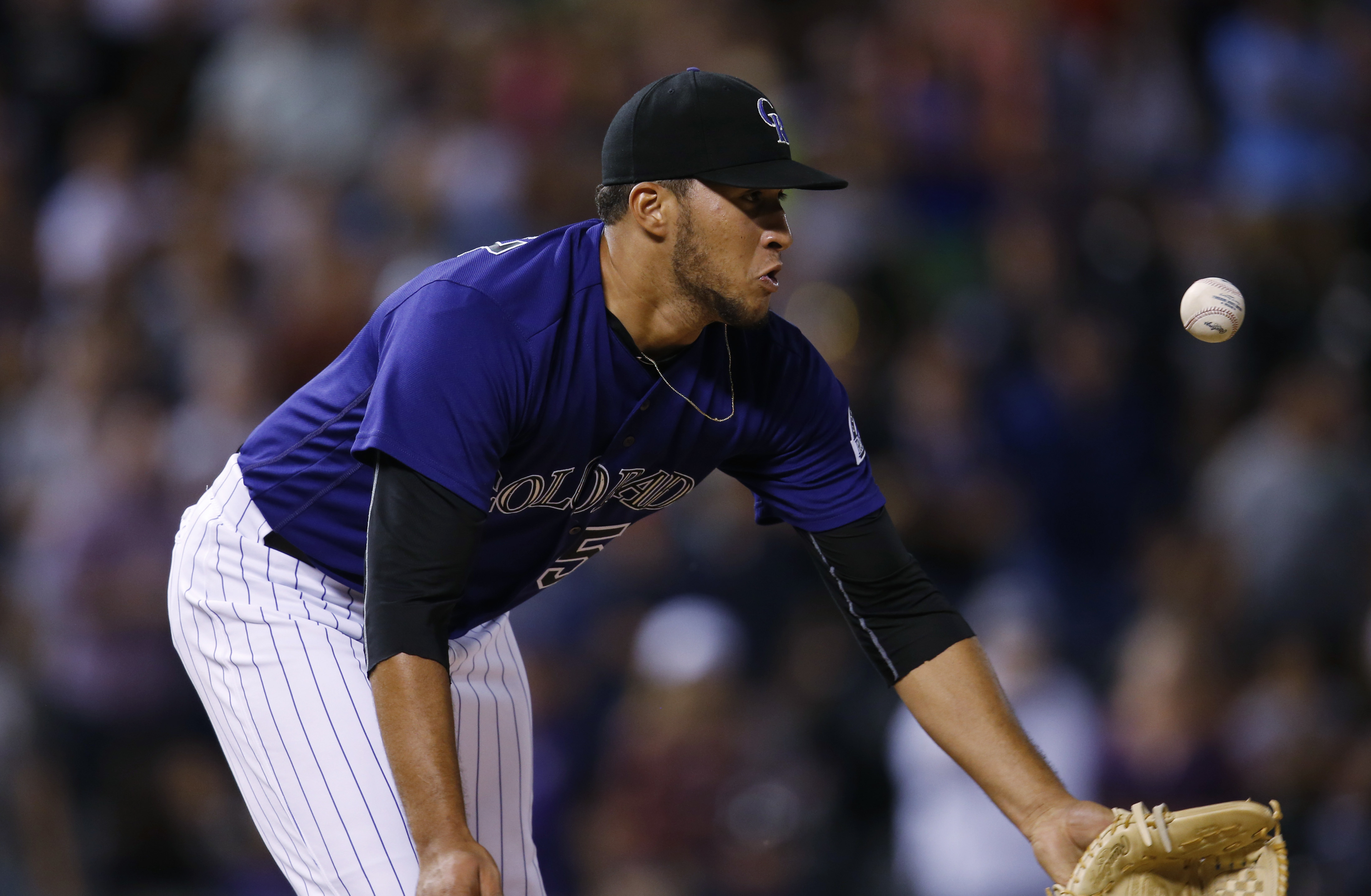 Colorado Rockies relief pitcher Carlos Estevez reaches out to field ground ball hit by Tampa Bay Rays' Logan Forsythe for the final out in the ninth inning of a baseball game Monday, July 18, 2016 in Denver. The Rockies won 7-4. (AP Photo/David Zalubowski