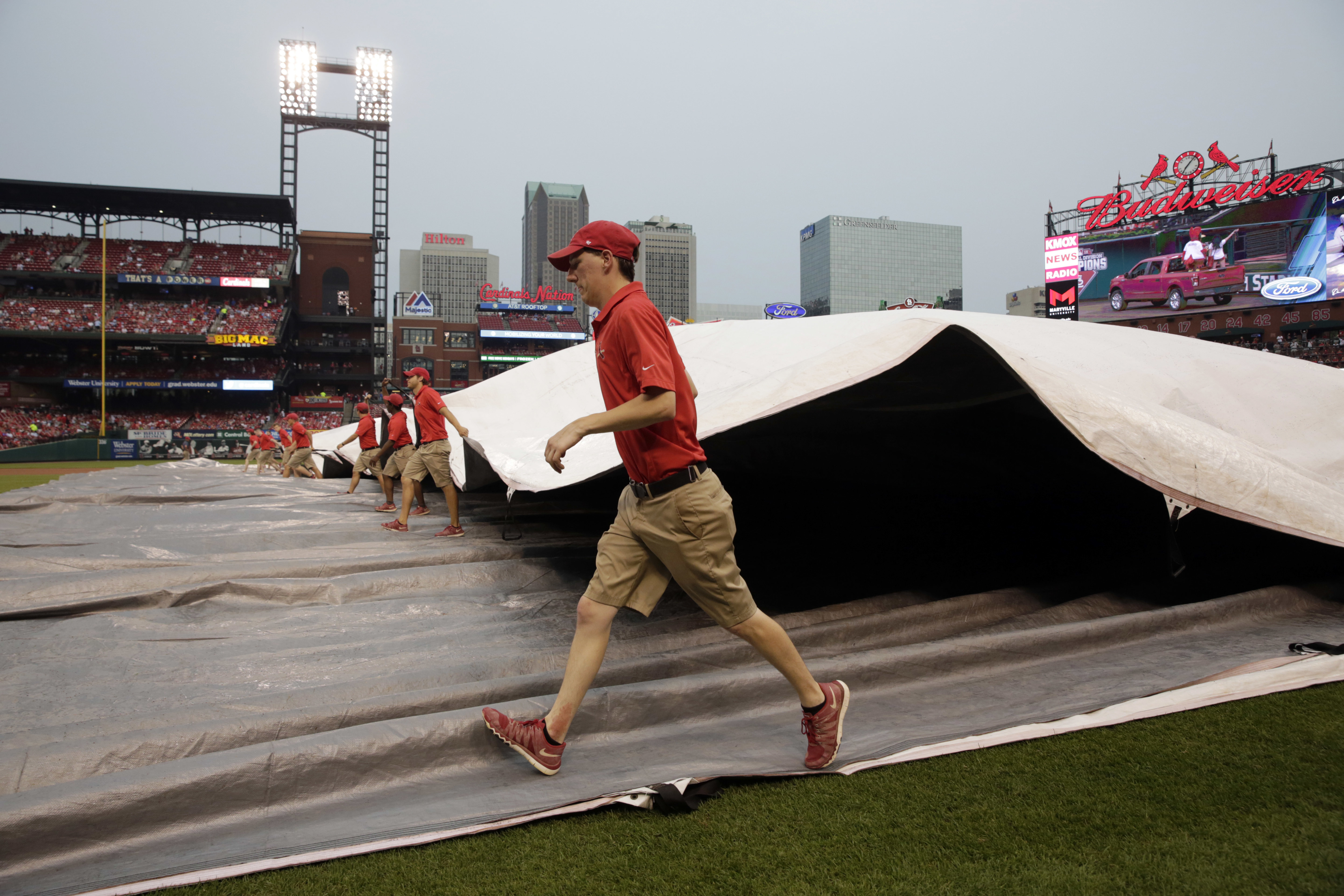 Members of the Busch Stadium grounds crew cover the field in anticipation of rain before the start of a baseball game between the St. Louis Cardinals and the San Diego Padres Tuesday, July 19, 2016, in St. Louis. (AP Photo/Jeff Roberson)