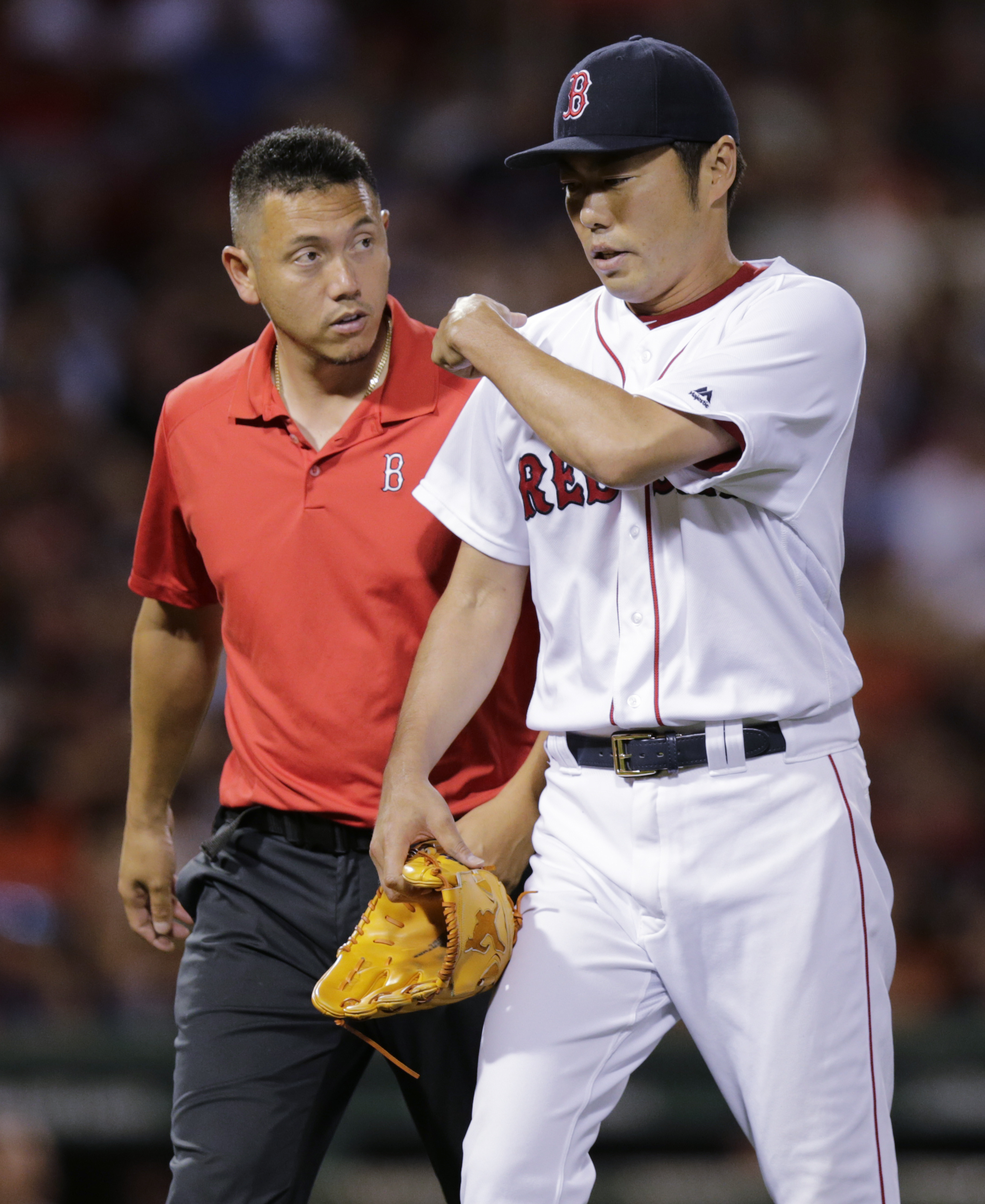 Boston Red Sox relief pitcher Koji Uehara is escorted to the dugout after an apparent injury during the ninth inning of a baseball game against the San Francisco Giants at Fenway Park, Tuesday, July 19, 2016, in Boston. (AP Photo/Charles Krupa)