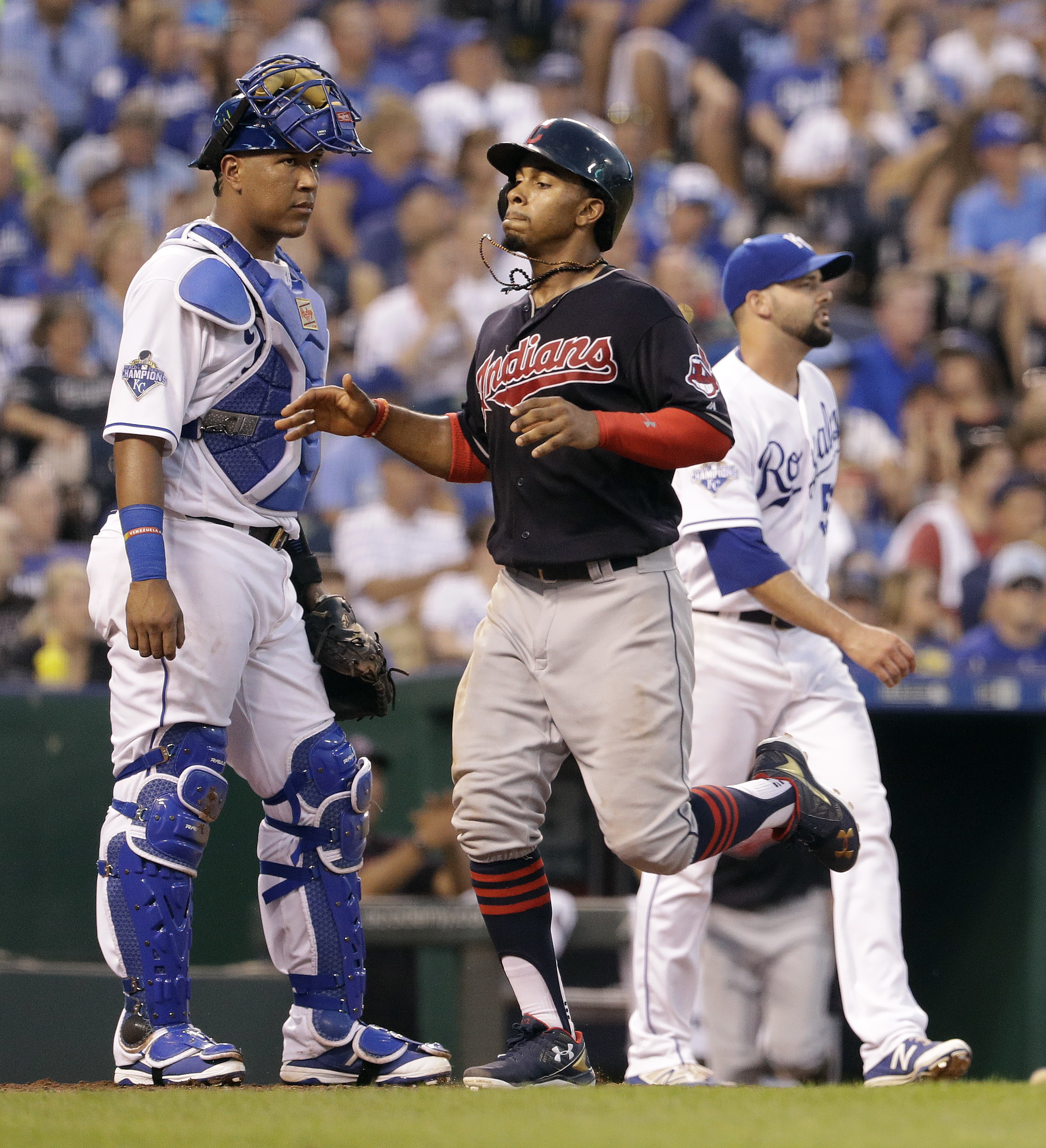 Cleveland Indians' Francisco Lindor runs past Kansas City Royals catcher Salvador Perez and relief pitcher Dillon Gee to score on a single by Carlos Santana during the fifth inning of a baseball game Tuesday, July 19, 2016, in Kansas City, Mo. (AP Photo/C