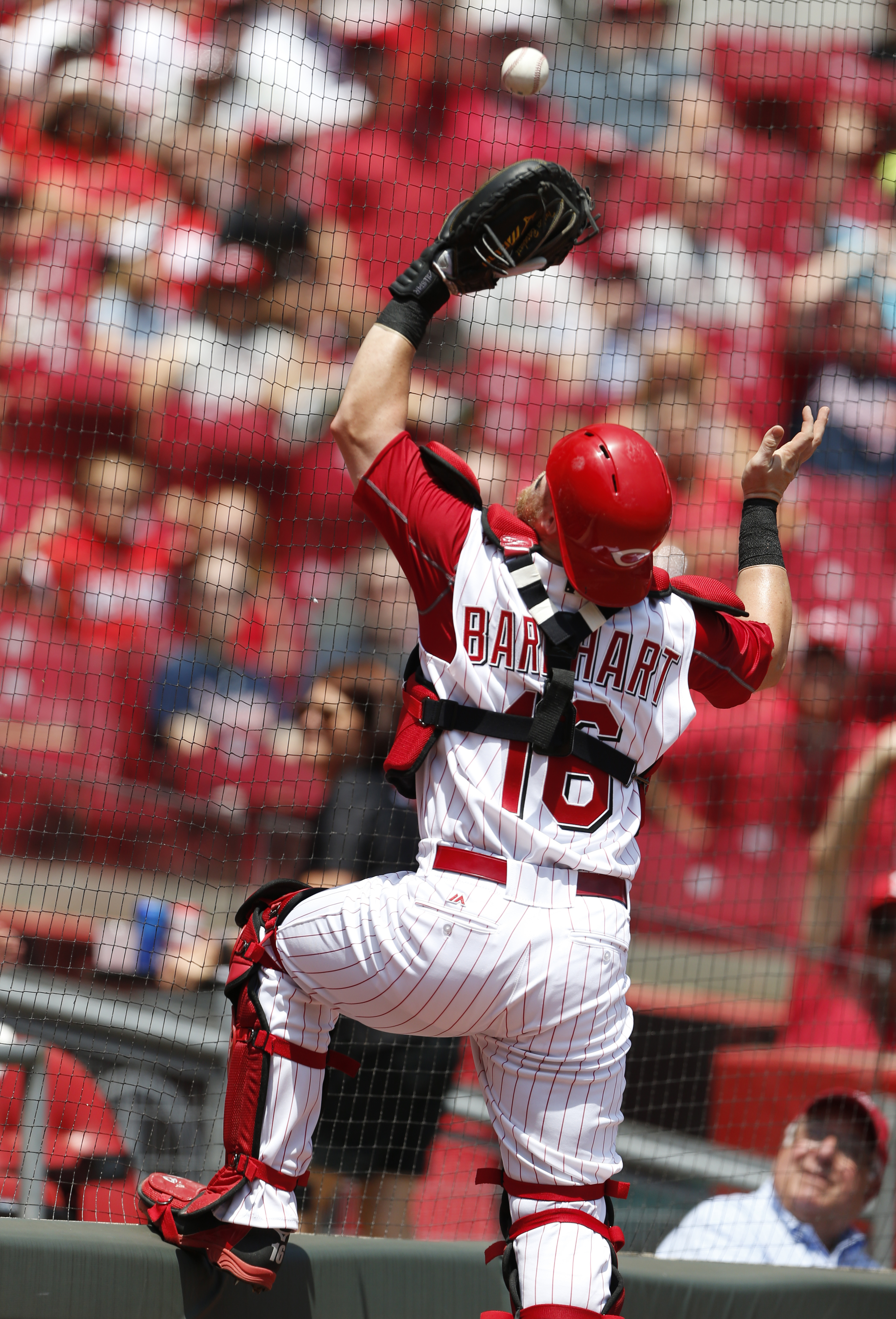 Cincinnati Reds catcher Tucker Barnhart climbs the fence behind home plate to catch a foul ball off the bat of Atlanta Braves' Ender Inciarte during the sixth inning of a baseball game, Wednesday, July 20, 2016, in Cincinnati. (AP Photo/Gary Landers)