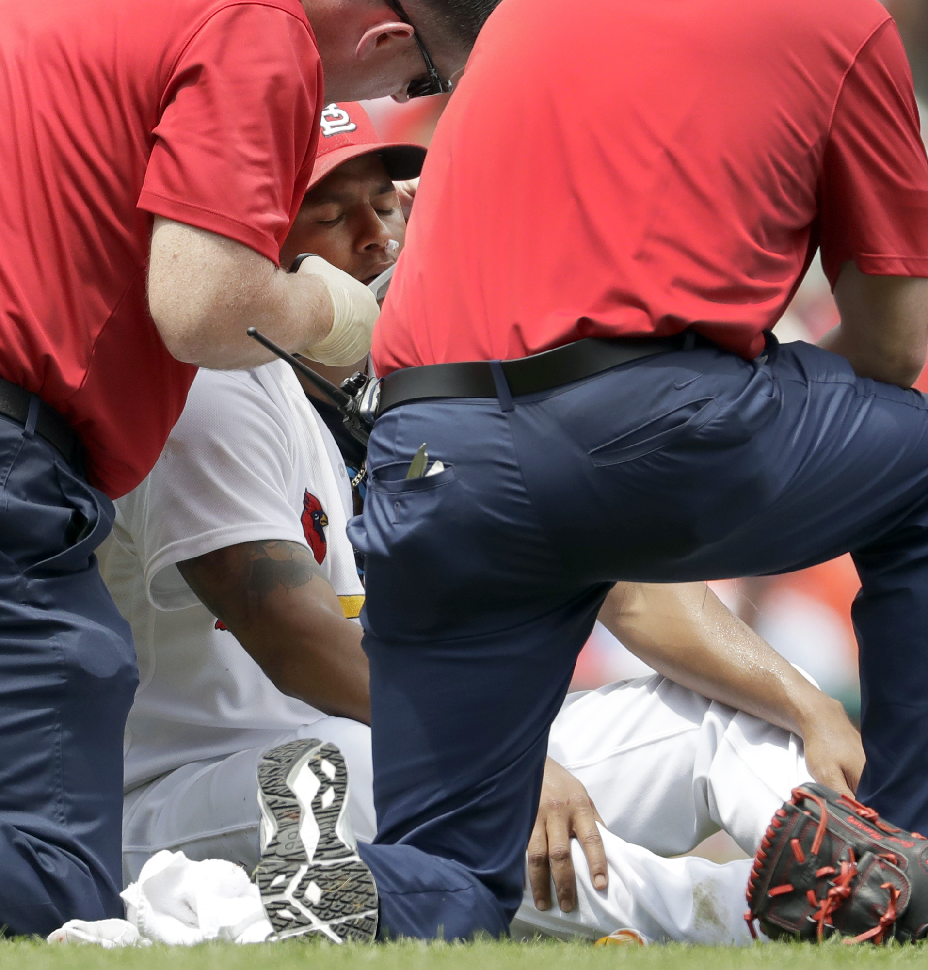 St. Louis Cardinals starting pitcher Carlos Martinez is tended to by trainers after getting a nose bleed during the second inning in the first game of a baseball doubleheader against the San Diego Padres Wednesday, July 20, 2016, in St. Louis. Martinez wa
