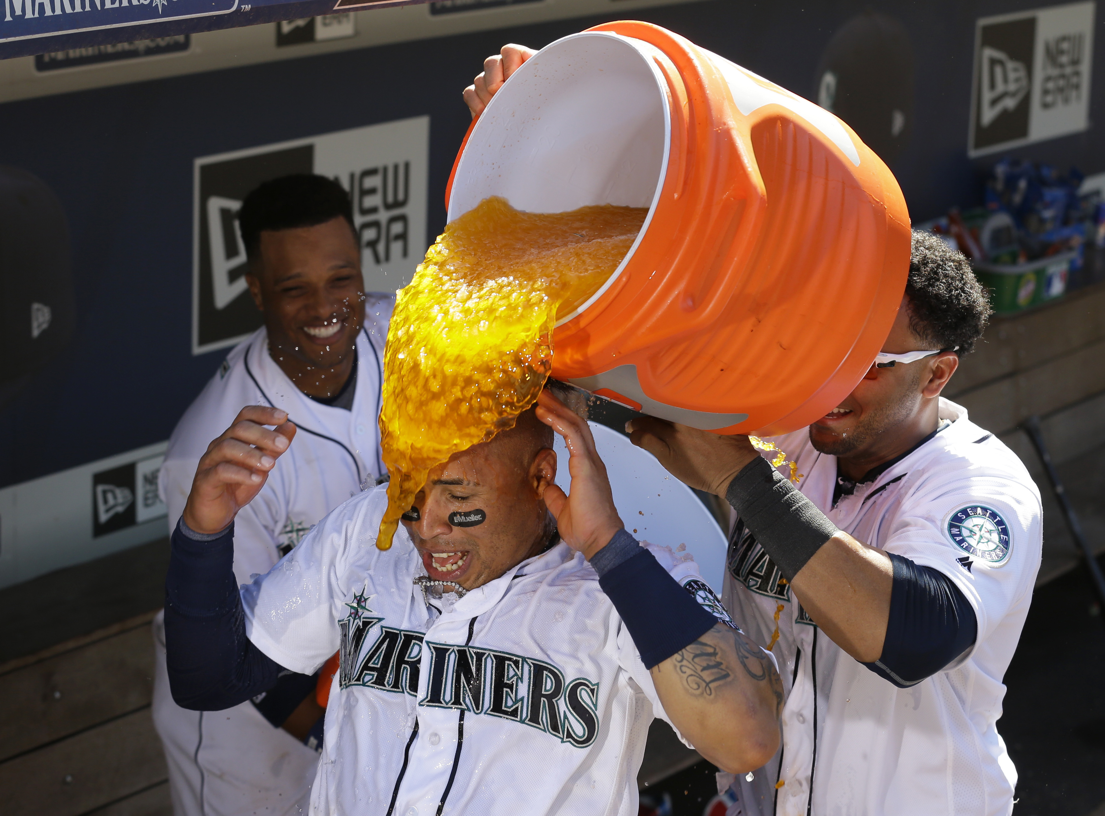 Seattle Mariners' Leonys Martin, center, is doused with water and sports drink by teammates Robinson Cano, left, and Nelson Cruz, right, after Martin hit a solo walk-off home run in the 11th inning of a baseball game to give the Mariners a 6-5 win over th