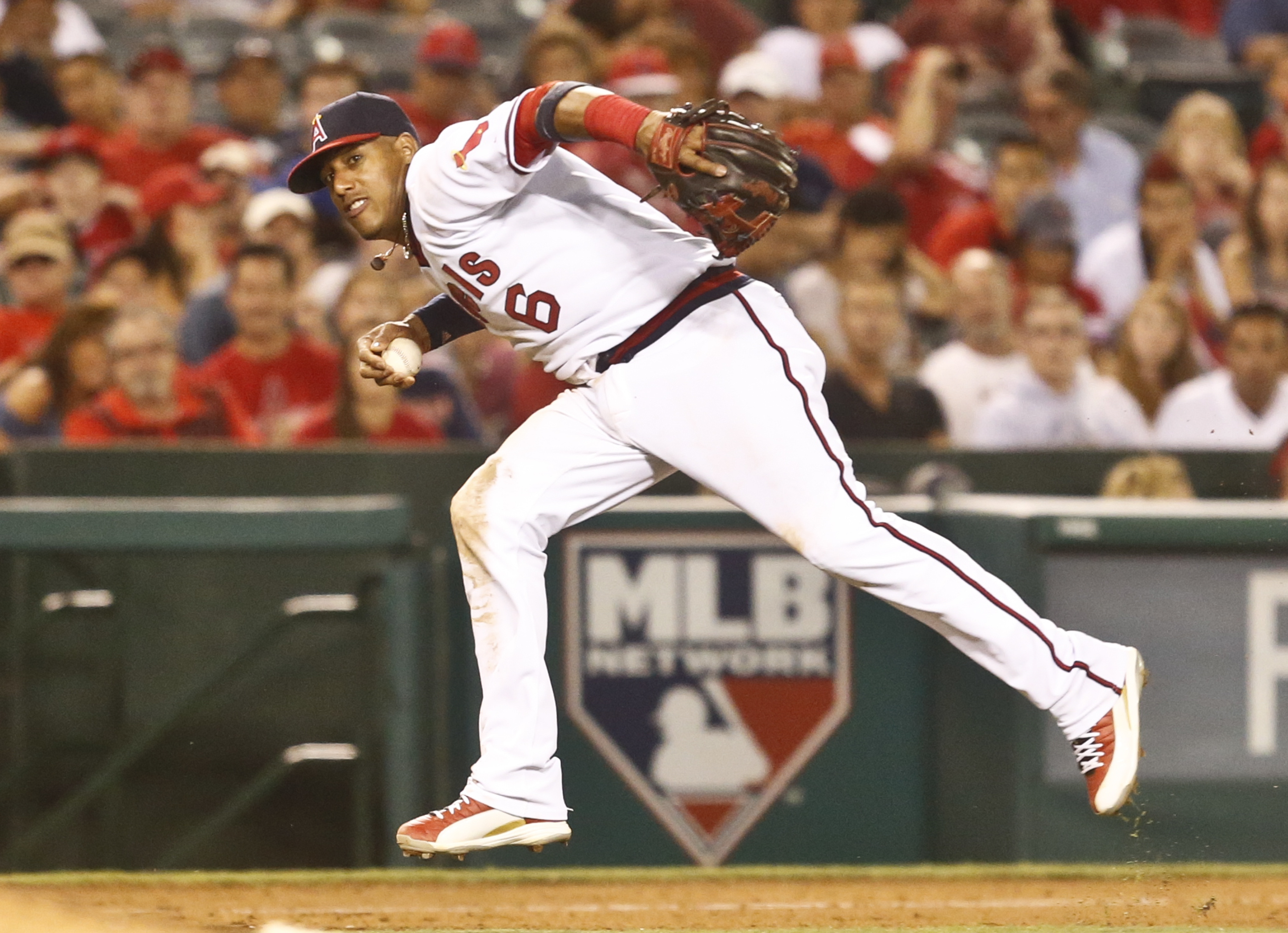 Los Angeles Angels third baseman Yunel Escobar looks toward first but decides not to throw after fielding a slow roller hit by Texas Rangers' Mitch Moreland in the eighth inning of a baseball game Wednesday, July 20, 2016, in Anaheim, Calif. (AP Photo/Len