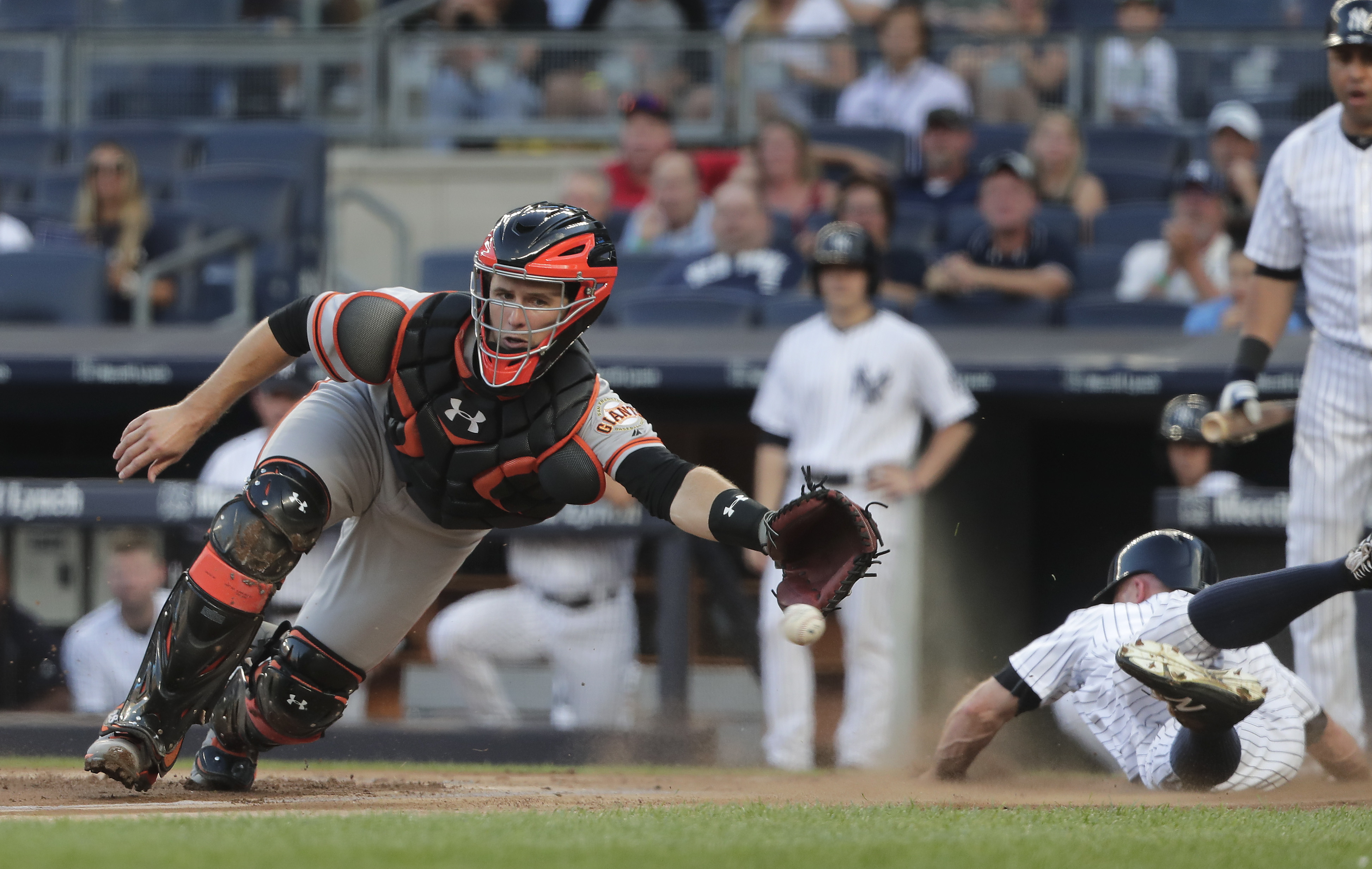 San Francisco Giants catcher Buster Posey can't reach the throw as New York Yankees' Brett Gardner, right, scores on a double by Starlin Castro during the first inning of a baseball game, Friday, July 22, 2016, in New York. (AP Photo/Julie Jacobson)