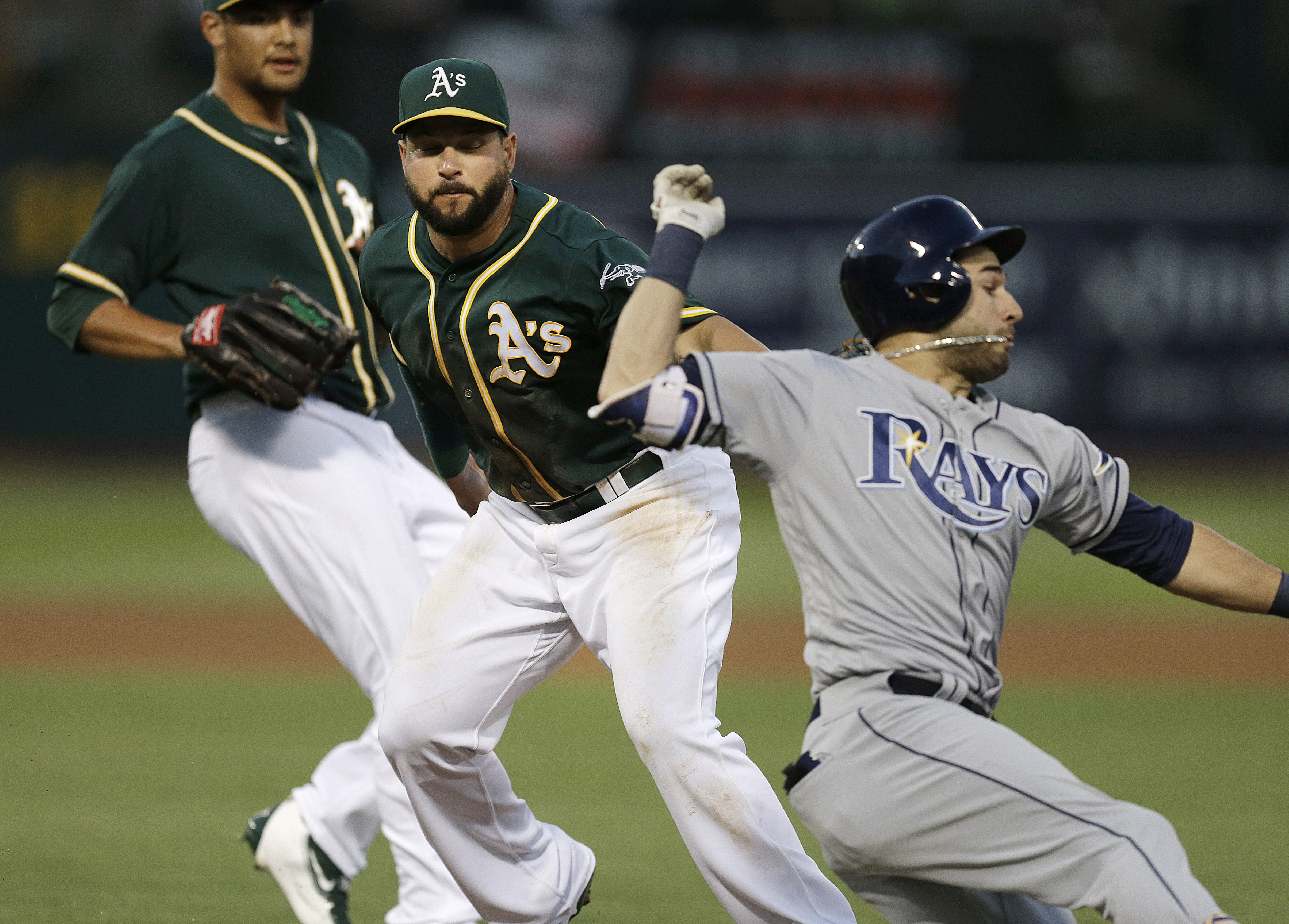Tampa Bay Rays' Kevin Kiermaier, right, is tagged out by Oakland Athletics' Yonder Alonso, center, at first base during the fifth inning of a baseball game Friday, July 22, 2016, in Oakland, Calif. At left is A's pitcher Sean Manaea. (AP Photo/Ben Margot)
