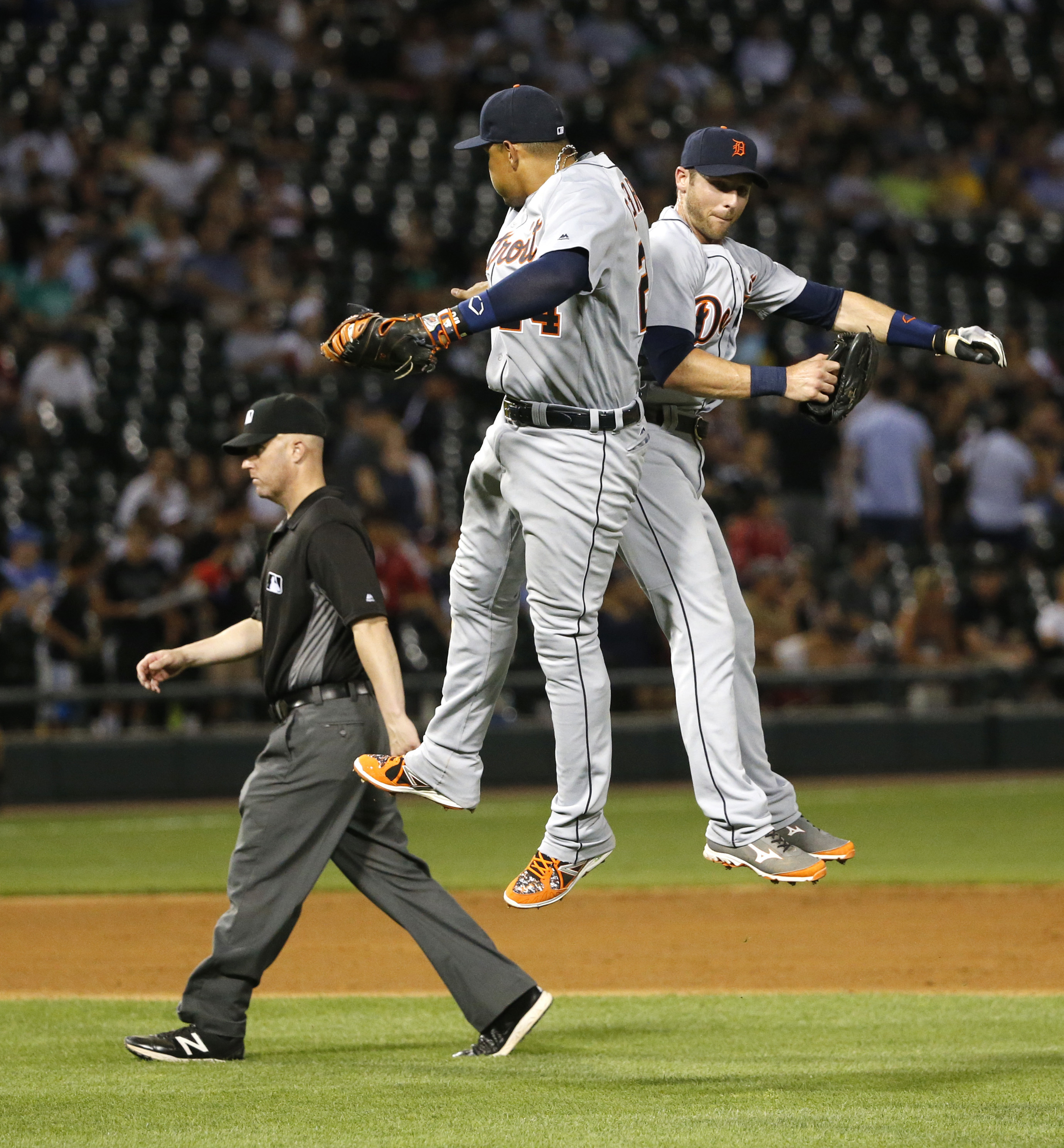 Detroit Tigers first baseman Miguel Cabrera, center, and third baseman Andrew Romine celebrate the Tigers' 7-5 win over the Chicago White Sox as second base umpire Ryan Blakney walks off the field after the baseball game Friday, July 22, 2016, in Chicago.