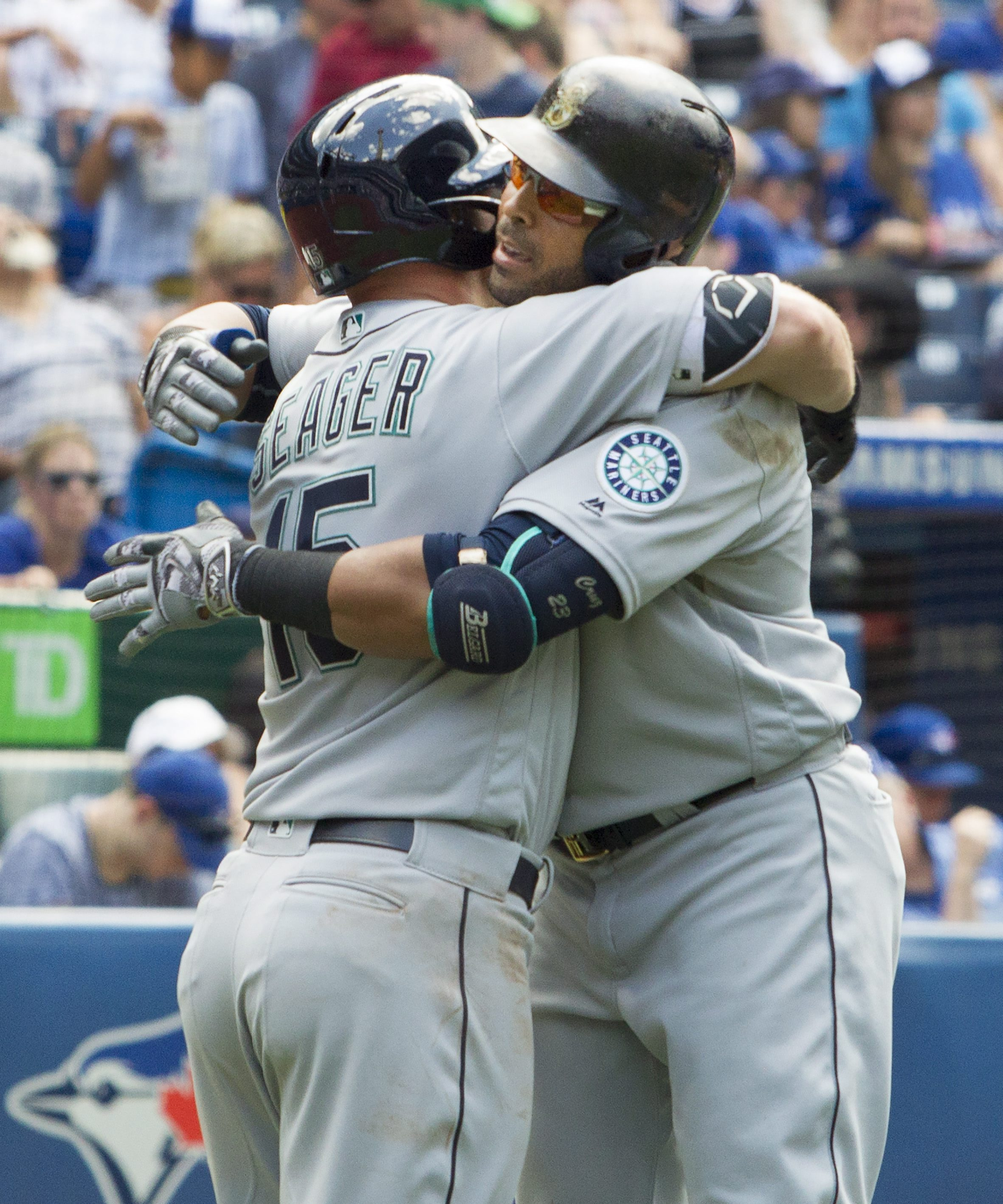 Seattle Mariners' Nelson Cruz, right, is embraced by teammate Kyle Seager after hitting a three-run home run in eighth-inning baseball game action against the Toronto Blue Jays in Toronto, Saturday, July 23, 2016. (Fred Thornhill/The Canadian Press via AP