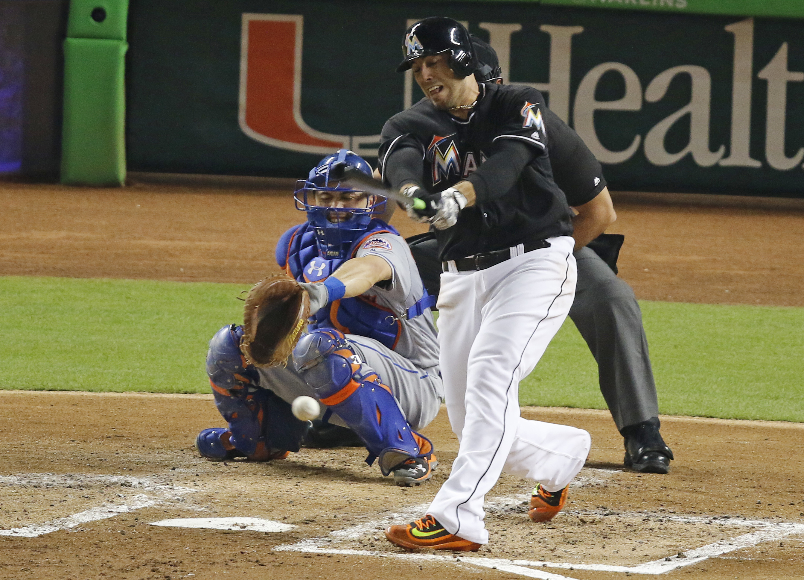 Miami Marlins' Jose Fernandez hits an RBI-single in the second inning in front of New York Mets catcher Travis d'Arnaud during a baseball game in Miami, Saturday, July 23, 2016. (AP Photo/Joe Skipper)
