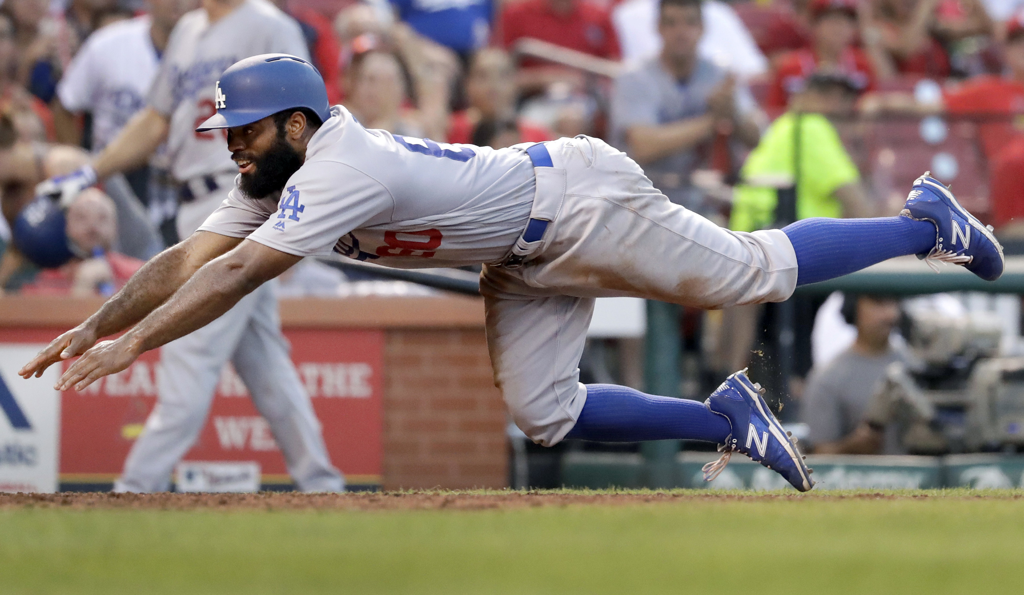Los Angeles Dodgers' Andrew Toles dives across home plate to score during the sixth inning of a baseball game against the St. Louis Cardinals, Saturday, July 23, 2016, in St. Louis. (AP Photo/Jeff Roberson)