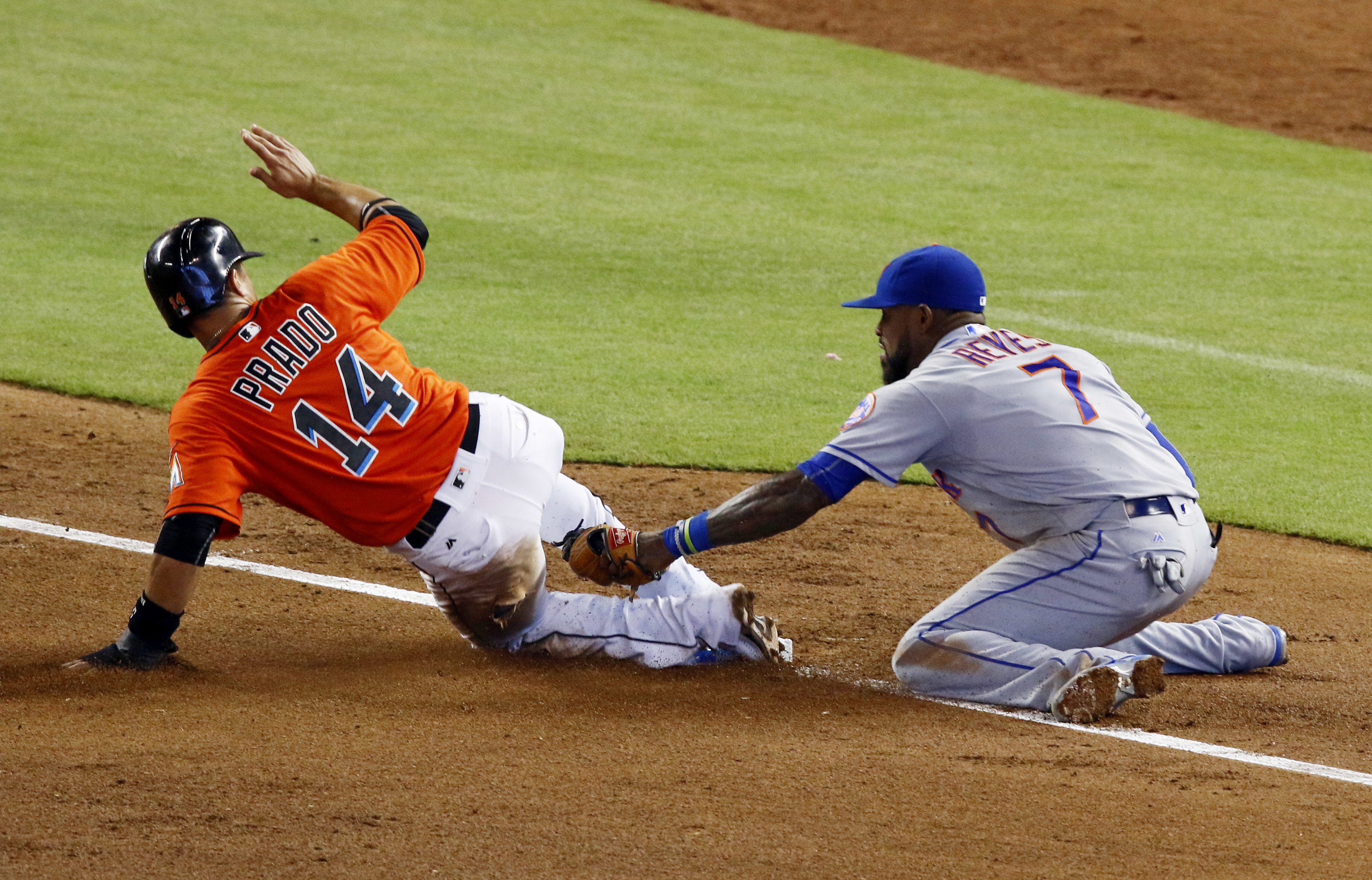 Miami Marlins' Martin Prado, left, slides safely into third base as New York Mets third baseman Jose Reyes (7) applies the late tag in the fifth inning of a baseball game in Miami, Sunday, July 24, 2016. (AP Photo/Joe Skipper)