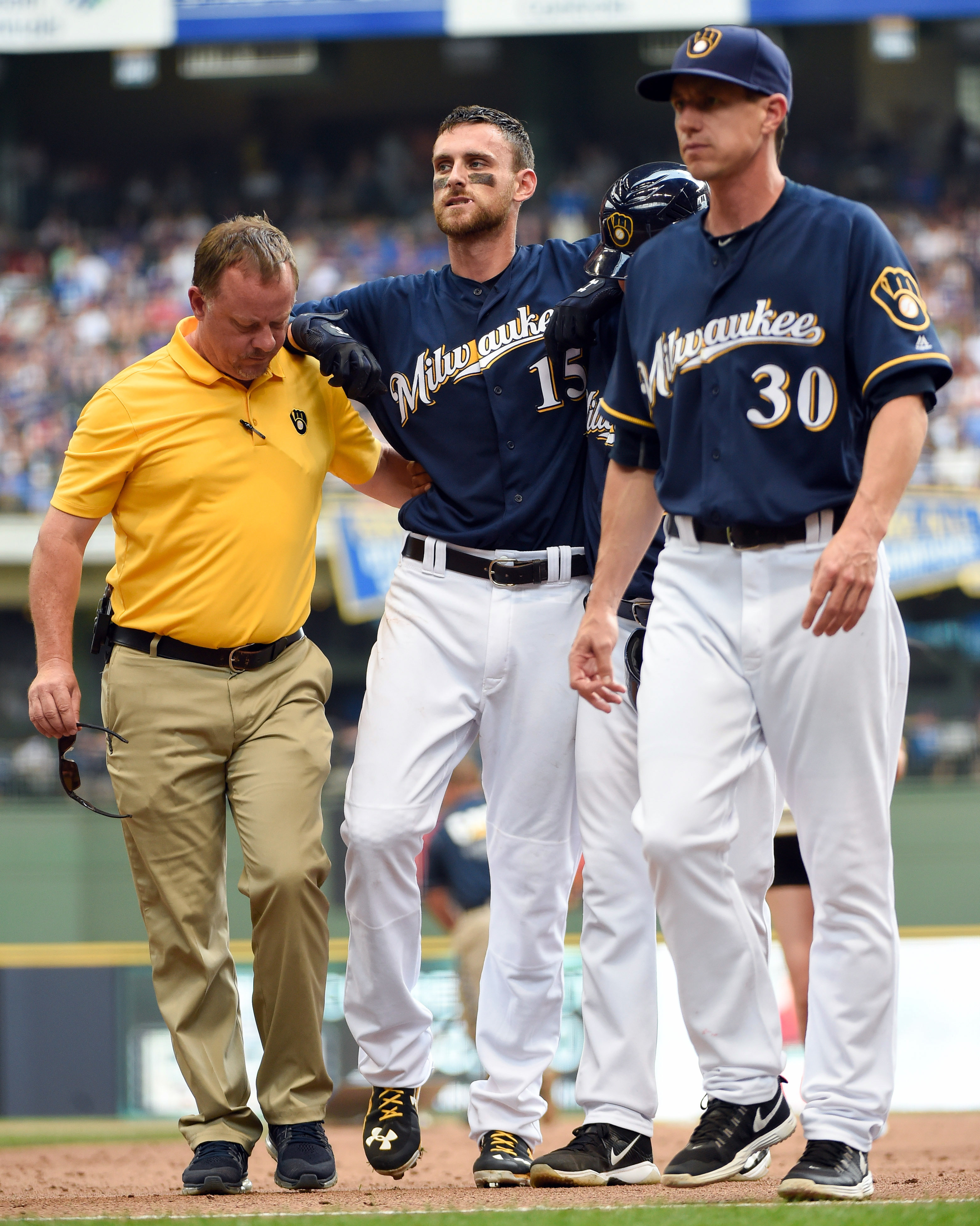 Milwaukee Brewers' Will Middlebrooks, center, is helped off the field by head athletic trainer Dan Wright, left, and manager Craig Counsell, right, with an injury after popping out during the third inning of a baseball game against the Chicago Cubs, Sunda