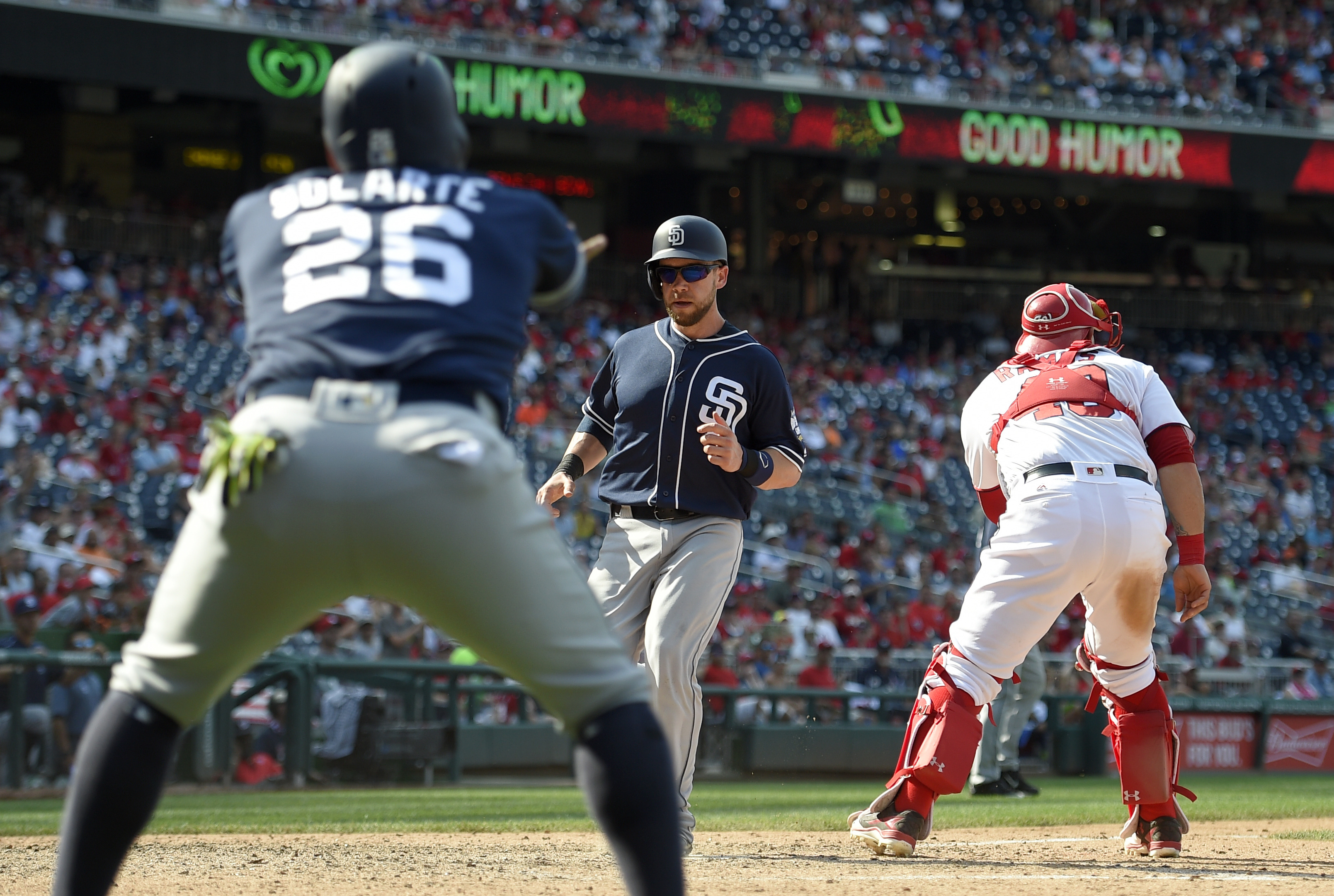 San Diego Padres' Ryan Schimpf, center, comes in to score during the ninth inning of a baseball game past Washington Nationals catcher Wilson Ramos, right, on a double by Alexei Ramirez, Sunday, July 24, 2016, in Washington. Padres' Yangervis Solarte (26)