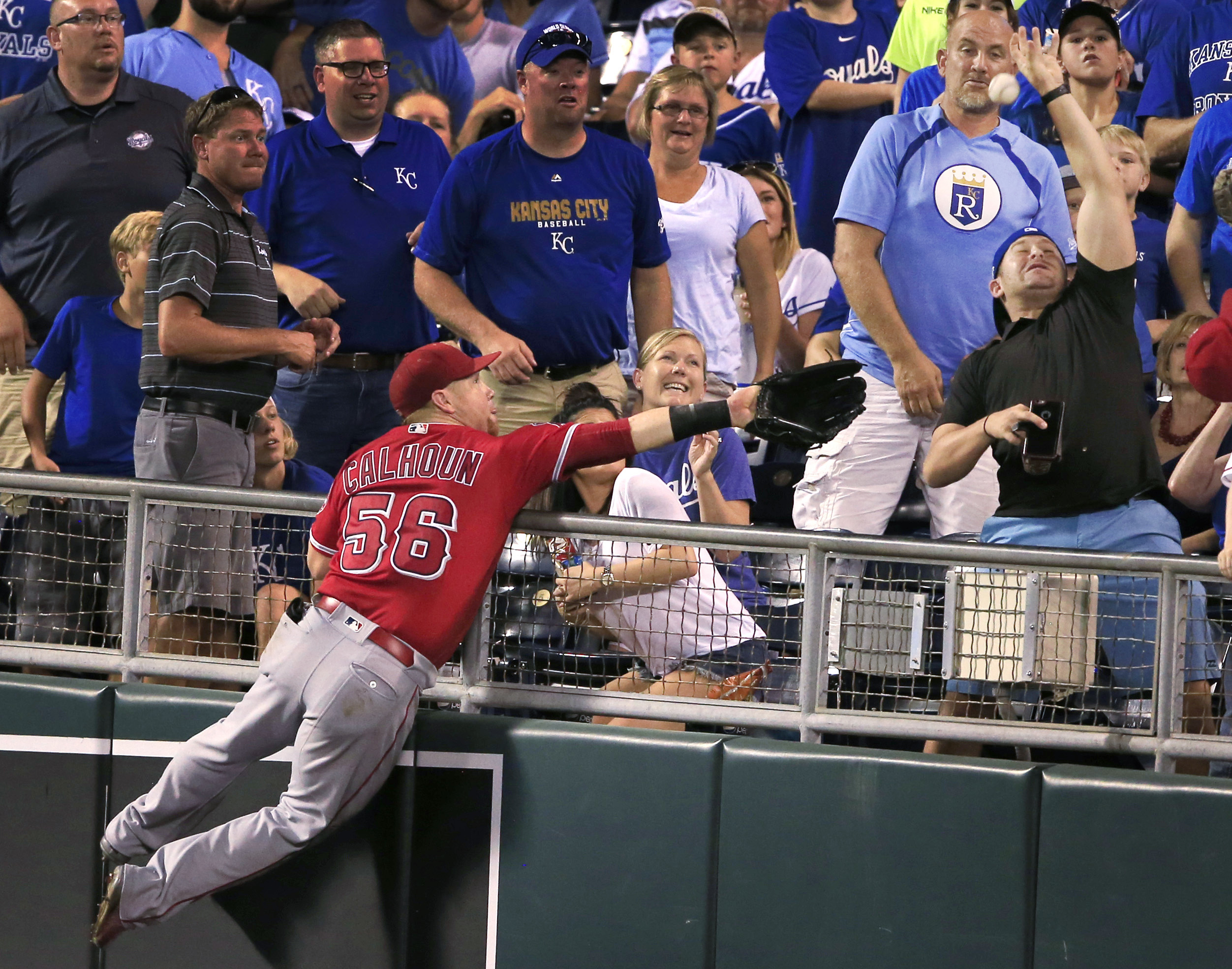 Los Angeles Angels right fielder Kole Calhoun leaps into the stands chasing a foul ball hit by Kansas City Royals' Alcides Escobar during the fifth inning of a baseball game at Kauffman Stadium in Kansas City, Mo., Monday, July 25, 2016. (AP Photo/Orlin W