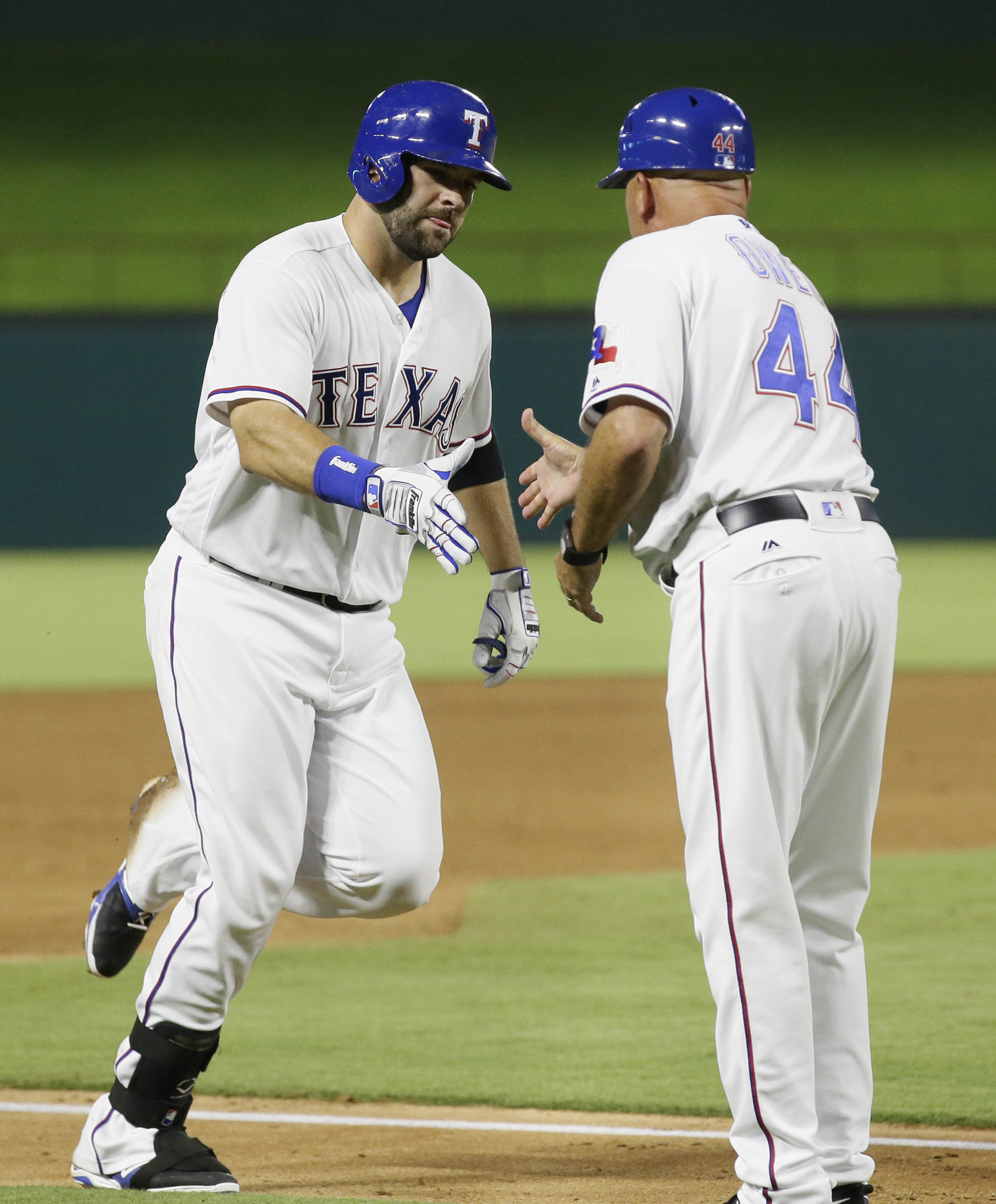 Texas Rangers' Mitch Moreland, left, is congratulated by third base coach Spike Owen (44) as Moreland runs the bases after hitting a two run home run during the fifth inning of a baseball game against the Oakland Athletics in Arlington, Texas, Tuesday, Ju