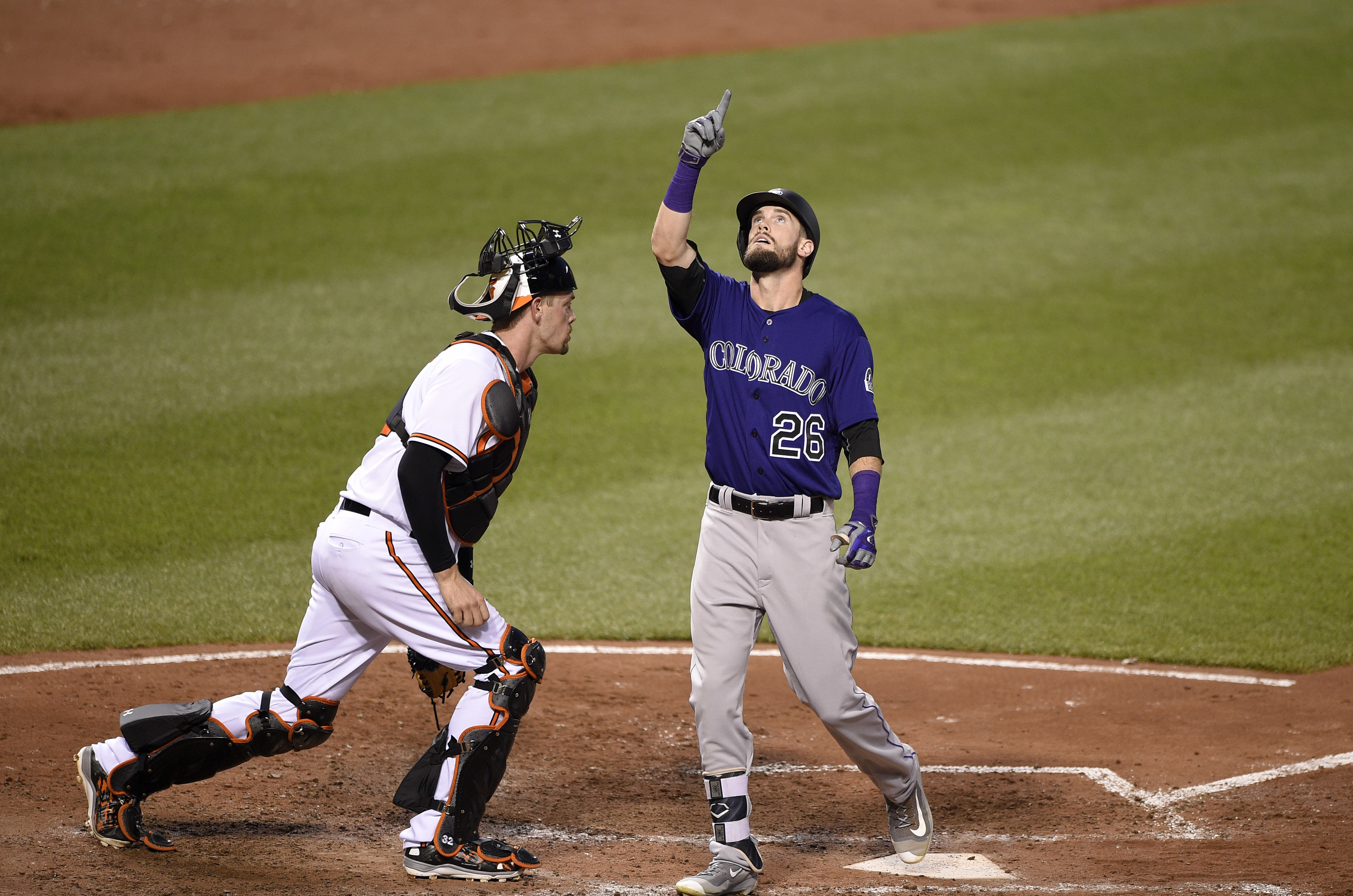 Colorado Rockies' David Dahl (26) celebrates his home run as Baltimore Orioles catcher Matt Wieters stands at left during the sixth inning of a baseball game, Wednesday, July 27, 2016, in Baltimore. (AP Photo/Nick Wass)