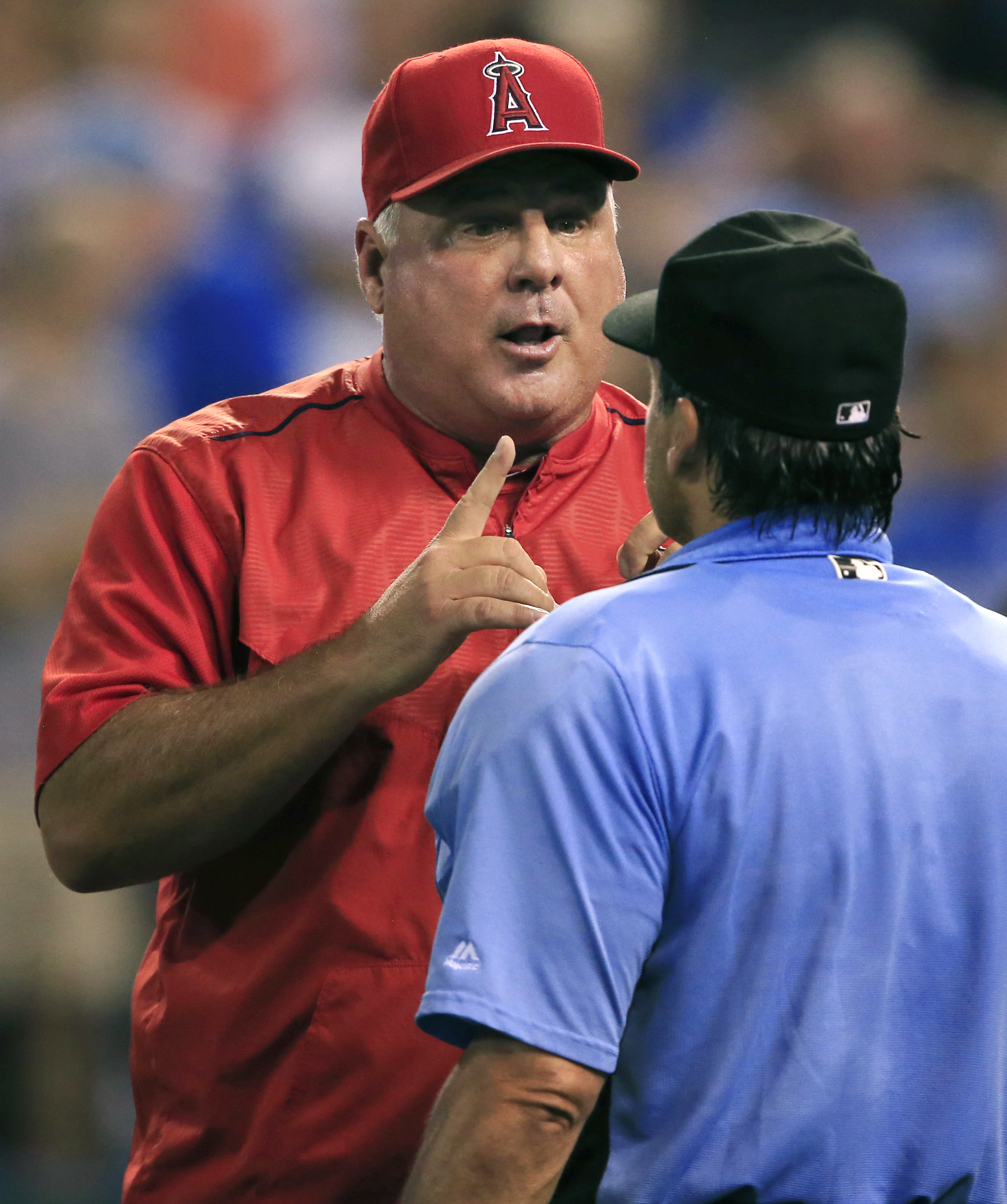 Los Angeles Angels manager Mike Scioscia, back, questions home plate umpire Phil Cuzzi during the seventh inning of a baseball game against the Kansas City Royals at Kauffman Stadium in Kansas City, Mo., Wednesday, July 27, 2016. (AP Photo/Orlin Wagner)