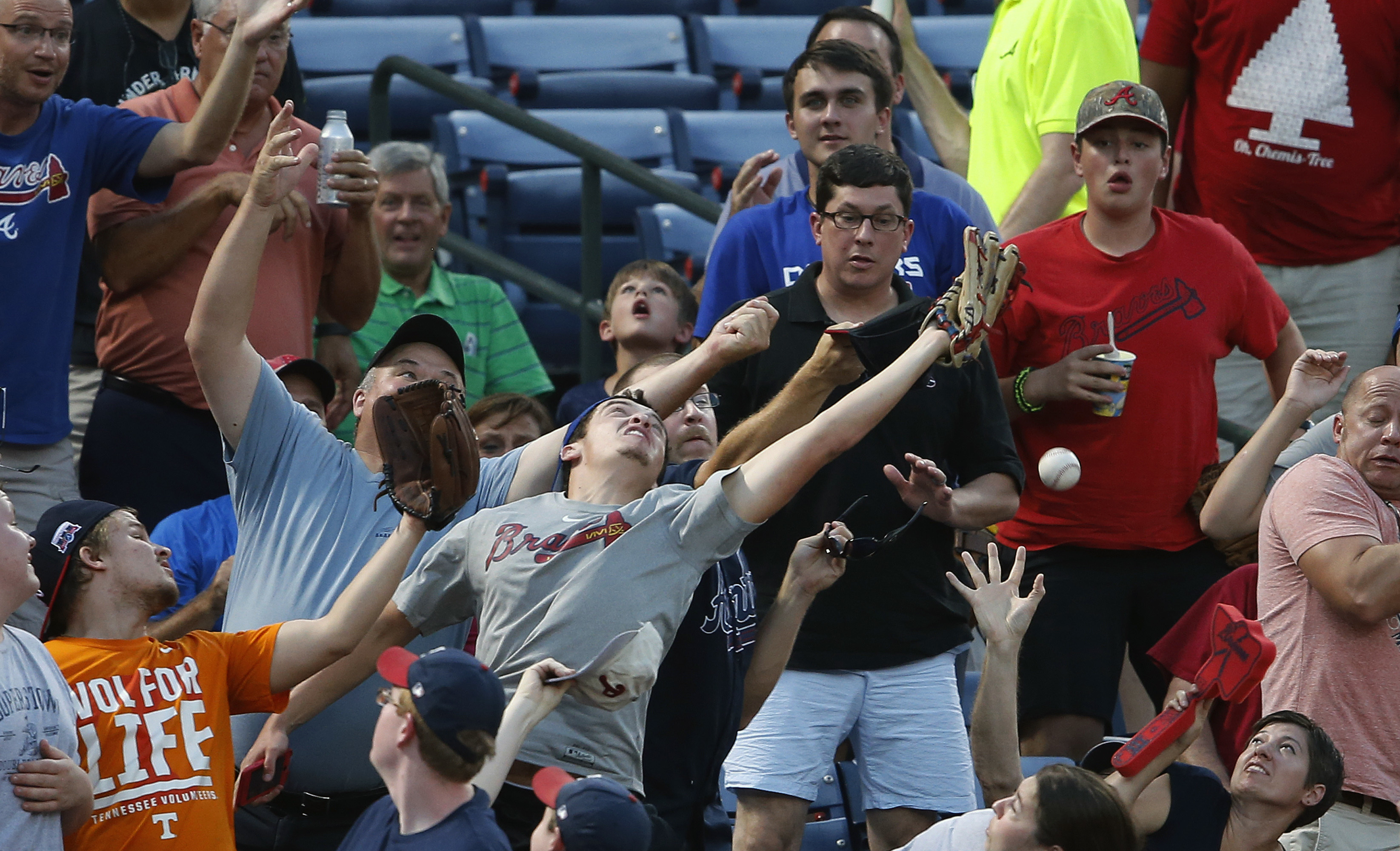 Fans reach for a foul ball during a baseball game between the Atlanta Braves and the Philadelphia Phillies, Friday, July 29, 2016, in Atlanta. (AP Photo/John Bazemore)