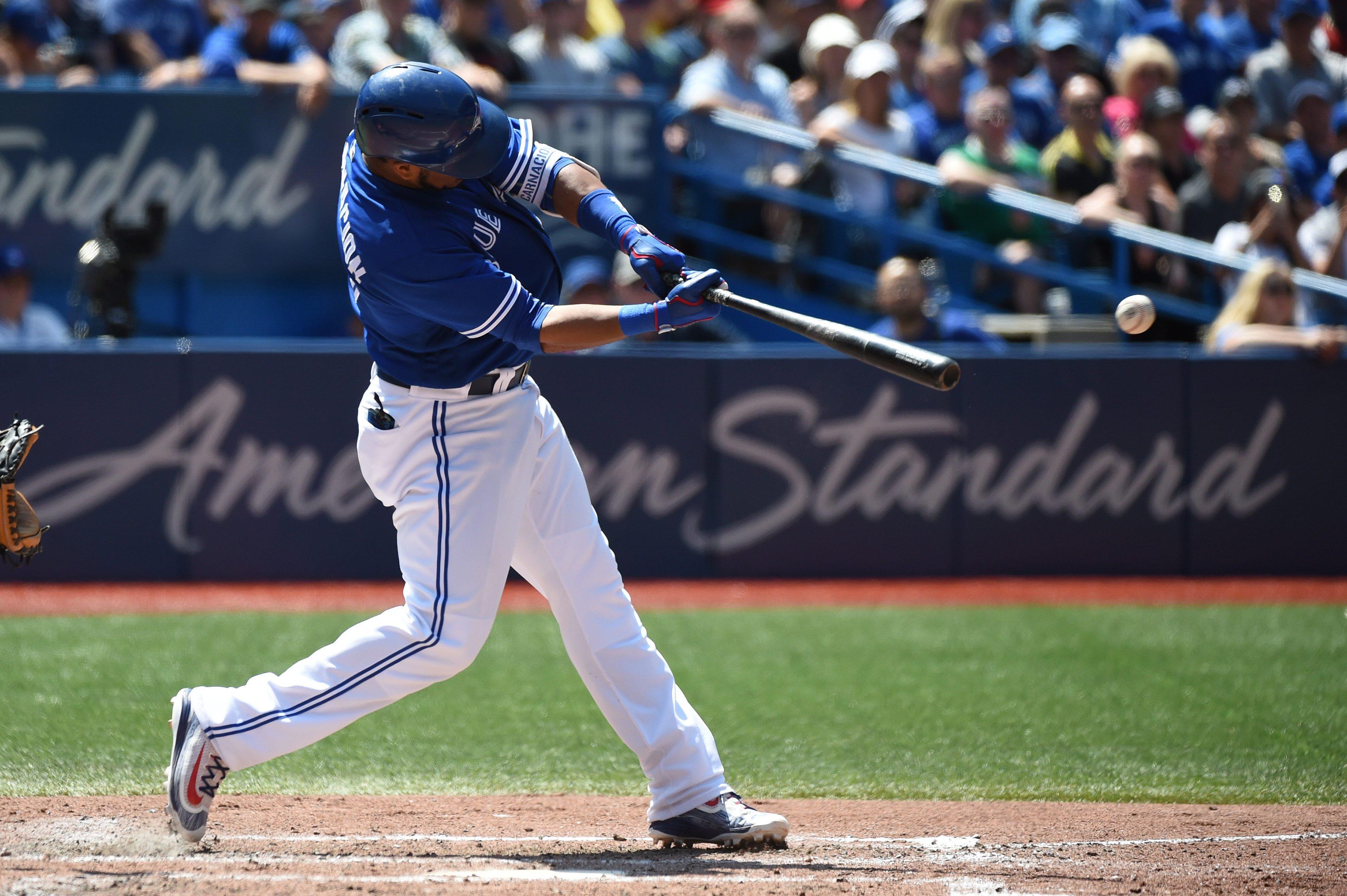 Toronto Blue Jays' Edwin Encarnacion hits an RBI double, scoring teammate Jose Bautista during the fifth inning of a baseball game, in Toronto on Saturday, July 30, 2016. (Jon Blacker/The Canadian Press via AP)