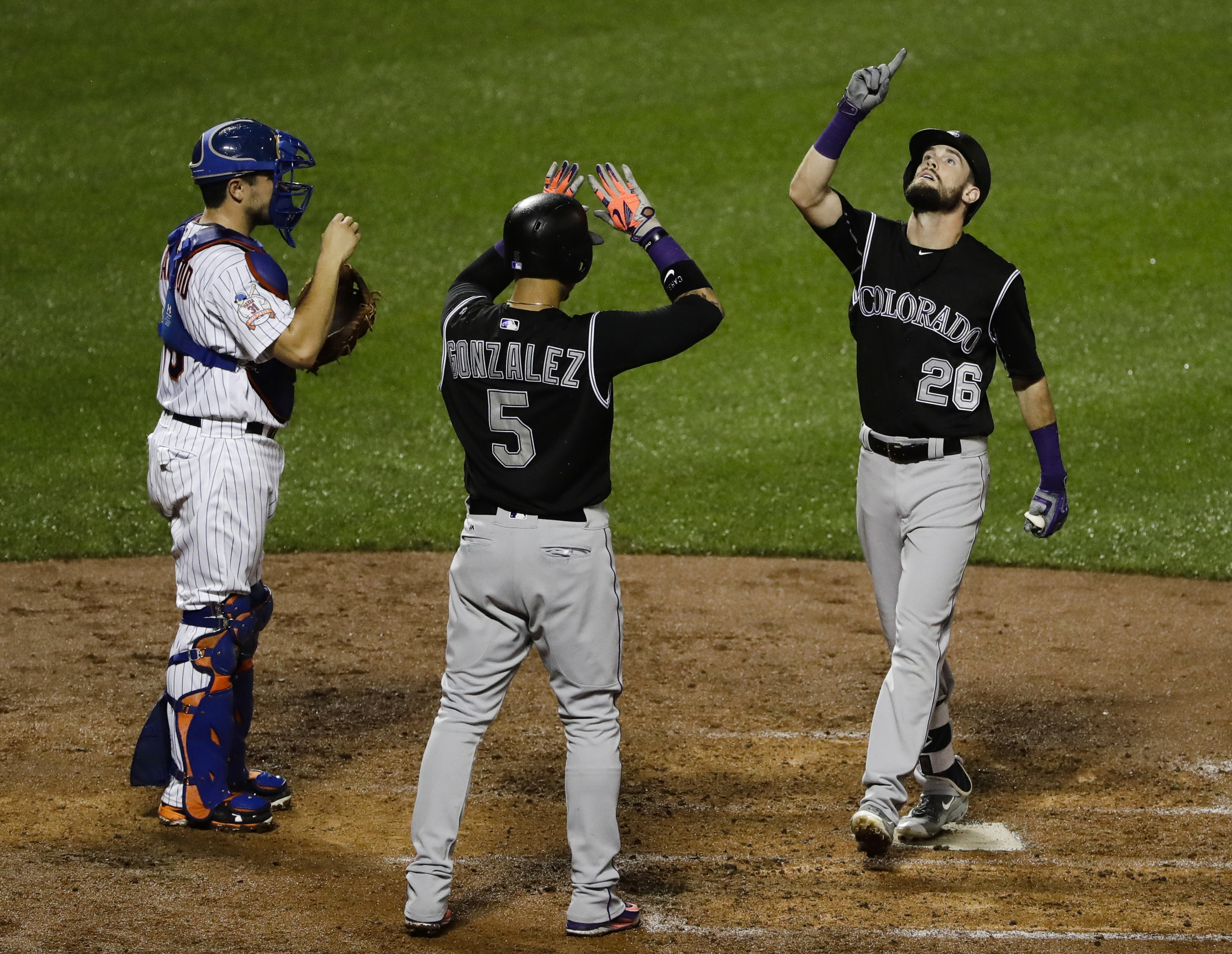 Colorado Rockies' David Dahl (26) and Carlos Gonzalez (5) celebrate after Dahl hit a two-run home run during the fourth inning of a baseball game as New York Mets catcher Travis d'Arnaud, left, watches, Saturday, July 30, 2016, in New York. (AP Photo/Fran