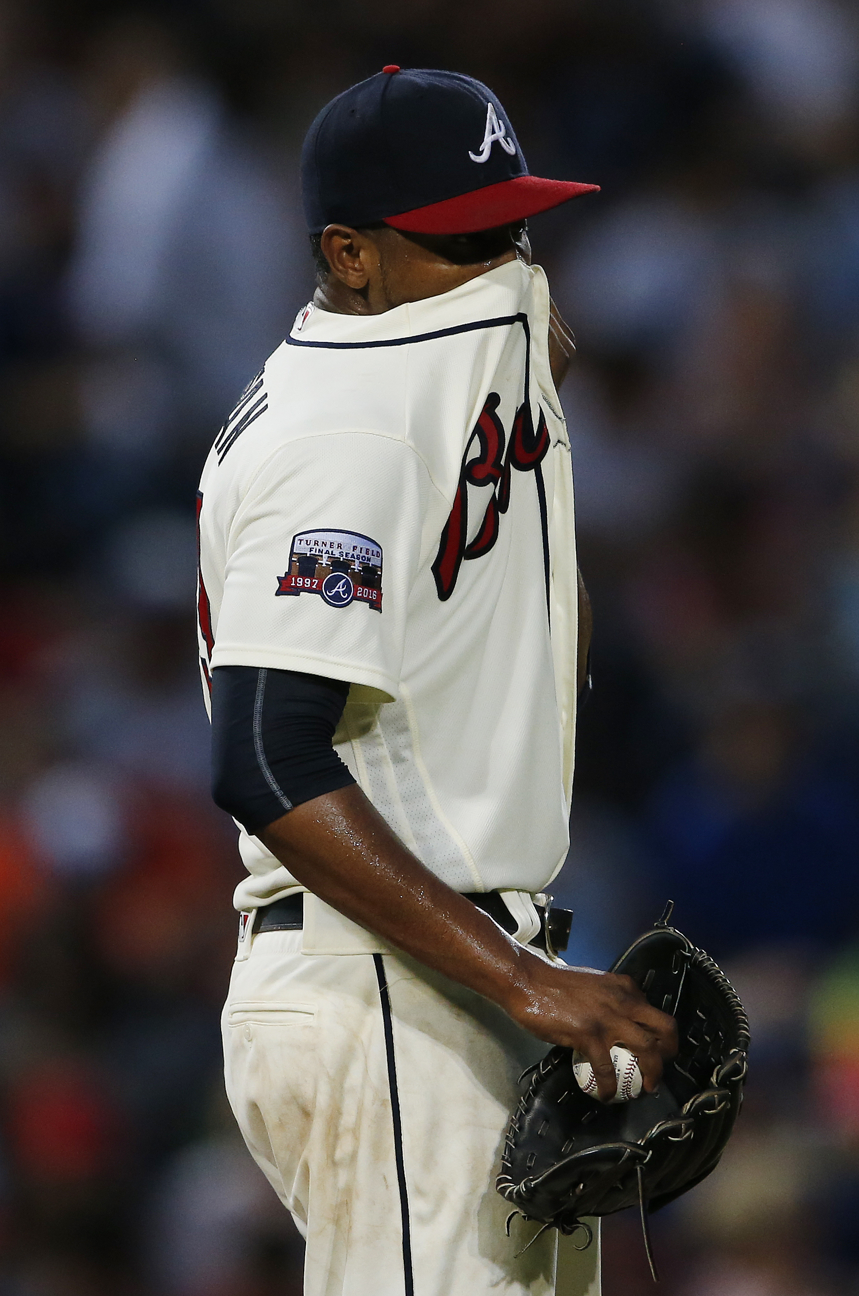 Atlanta Braves starting pitcher Julio Teheran wipes his face in the fifth inning of a baseball game against the Philadelphia Phillies, Saturday, July 30, 2016, in Atlanta. (AP Photo/John Bazemore)