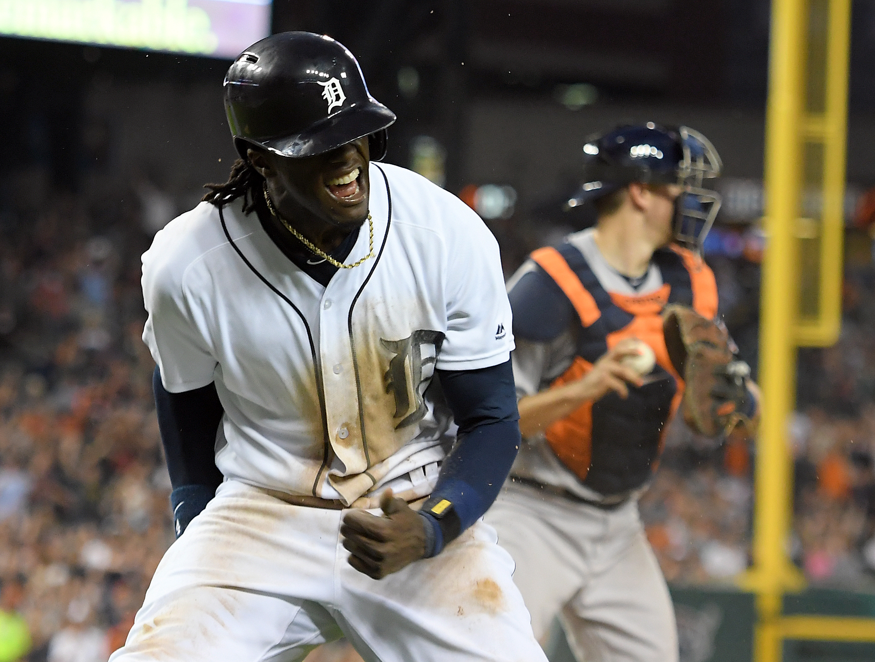 Detroit Tigers' Cameron Maybin celebrates after scoring  a run in the sixth inning after Astros second baseman Jose Altuve dropped a pop fly off the bat of Miguel Cabrera in shallow right field with two outs, in a baseball game Saturday, July 30, 2016, in