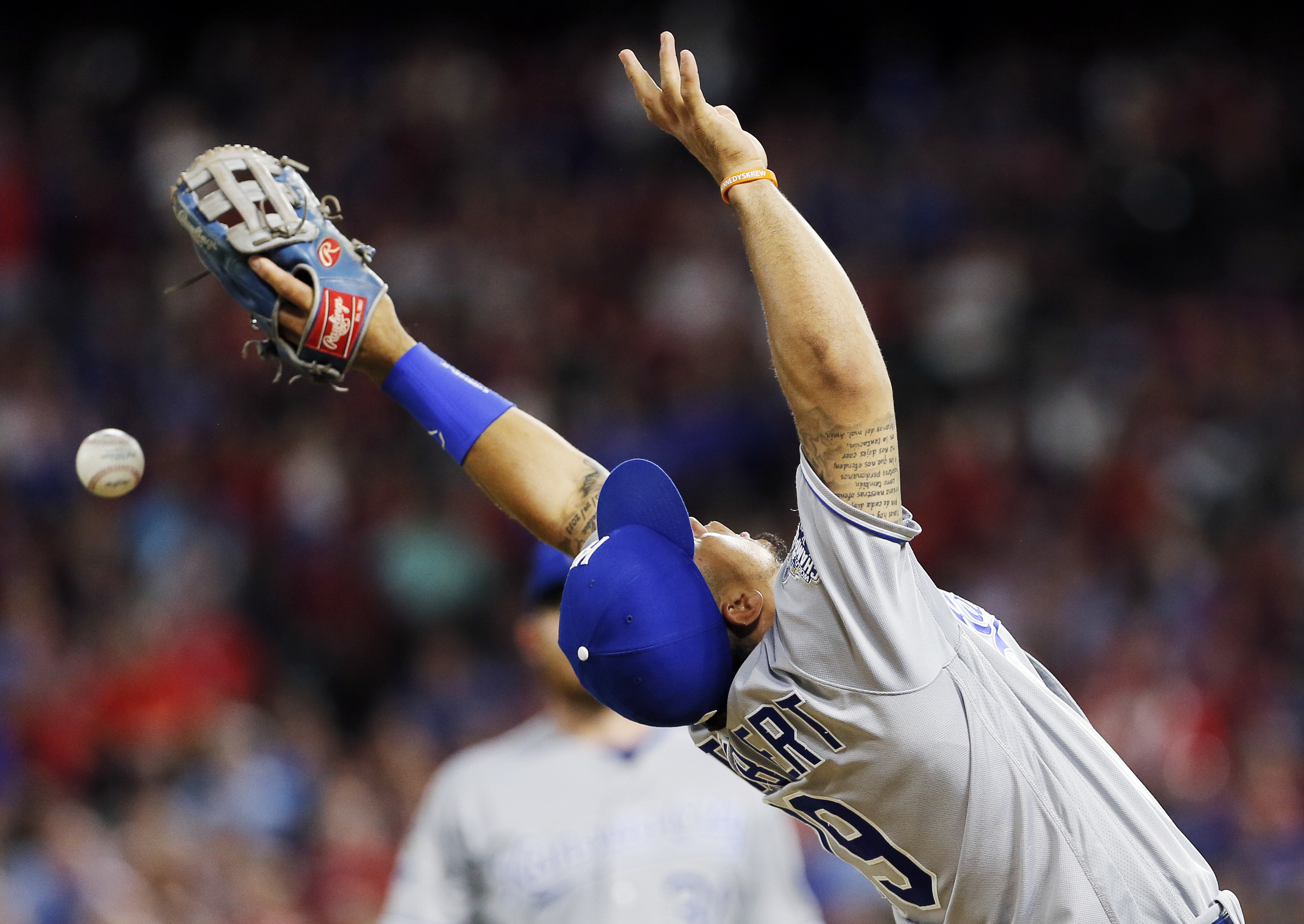 Kansas City Royals third baseman Cheslor Cuthbert (19) is unable to catch a pop fly hit by Texas Rangers' Mitch Moreland during the fifth inning of a baseball game, Saturday, July 30, 2016, in Arlington, Texas. Umpire Chris Conroy initially ruled that the