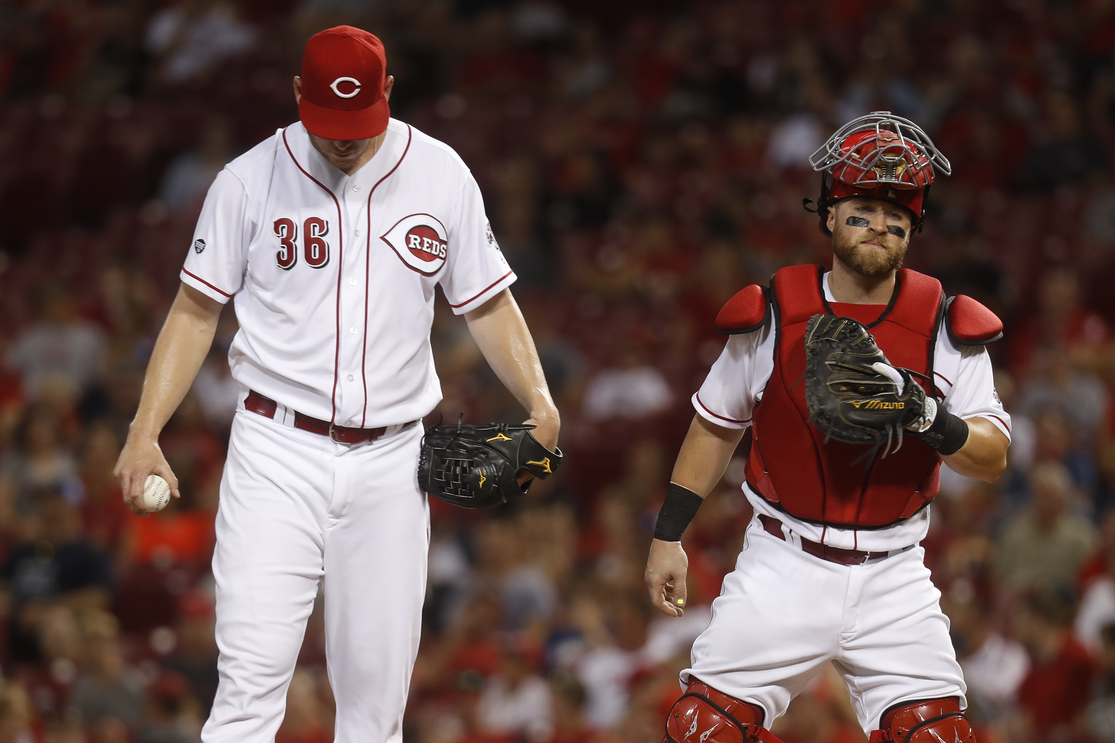 Cincinnati Reds relief pitcher Blake Wood (36) meets with catcher Tucker Barnhart, right, after giving up a solo home run to St. Louis Cardinals' Tommy Pham during the eighth inning of a baseball game, Tuesday, Aug. 2, 2016, in Cincinnati. (AP Photo/John