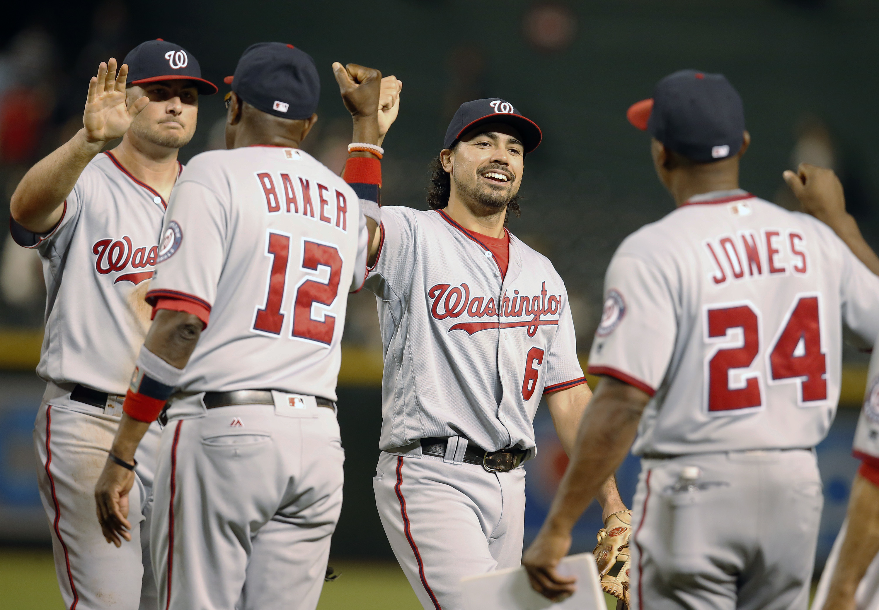Washington Nationals' Anthony Rendon (6) celebrates with Dusty Baker (12) and Jacque Jones after the Nationals defeated the Arizona Diamondbacks 10-4 during a baseball game, Tuesday, Aug. 2, 2016, in Phoenix. (AP Photo/Rick Scuteri)