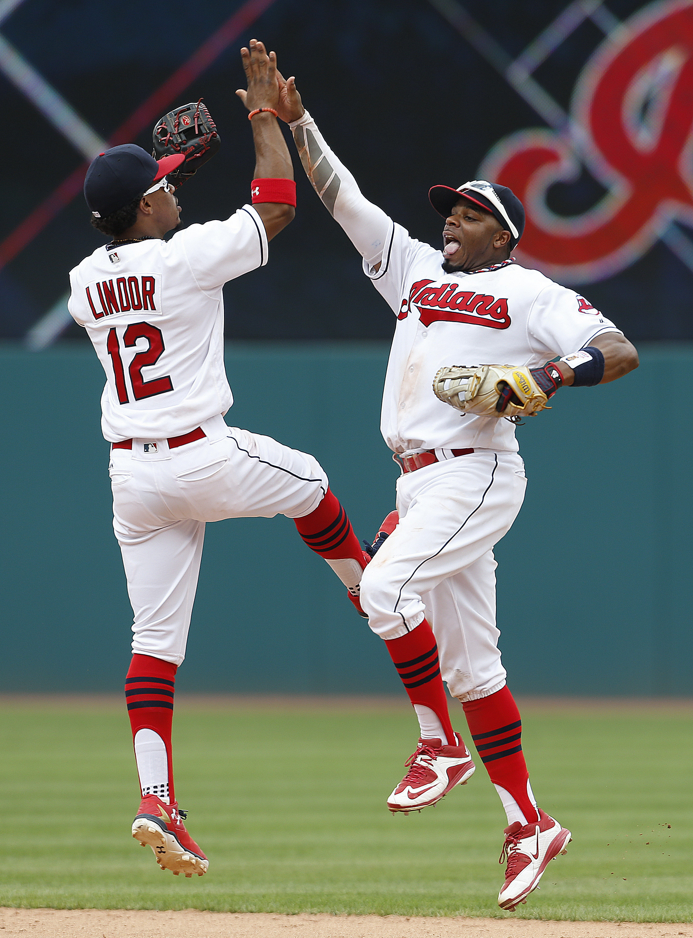 Cleveland Indians' Francisco Lindor (12) and Rajai Davis (20) celebrate a 9-2 win over the Minnesota Twins in a baseball game Thursday, Aug. 4, 2016, in Cleveland. (AP Photo/Ron Schwane)
