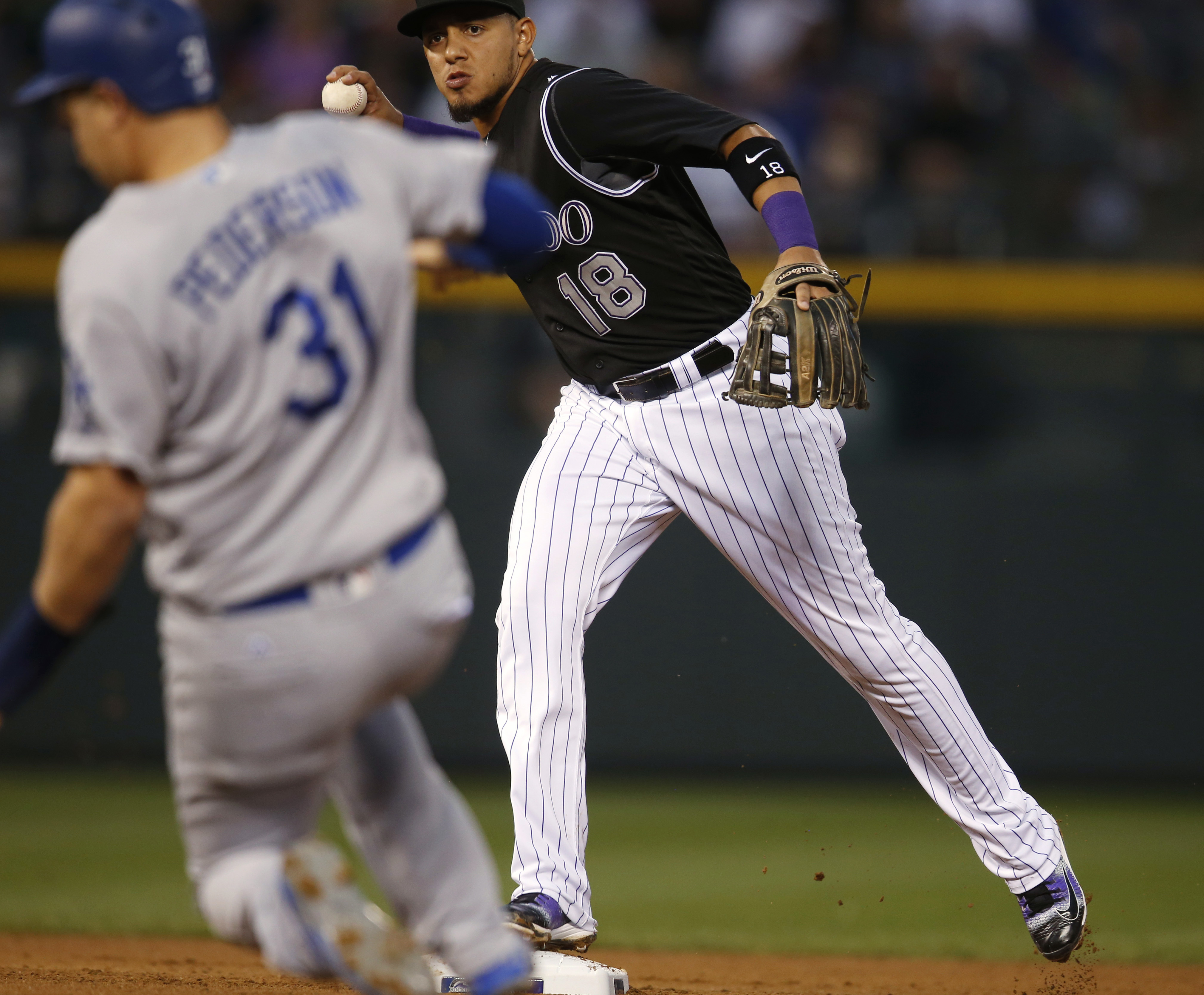 Colorado Rockies second baseman Cristhian Adames, back, forces out Los Angeles Dodgers' Joc Pederson at second base on the front end of a double play hit into by Kenta Maeda to end the top of the fourth inning of a baseball game Thursday, Aug. 4, 2016 in