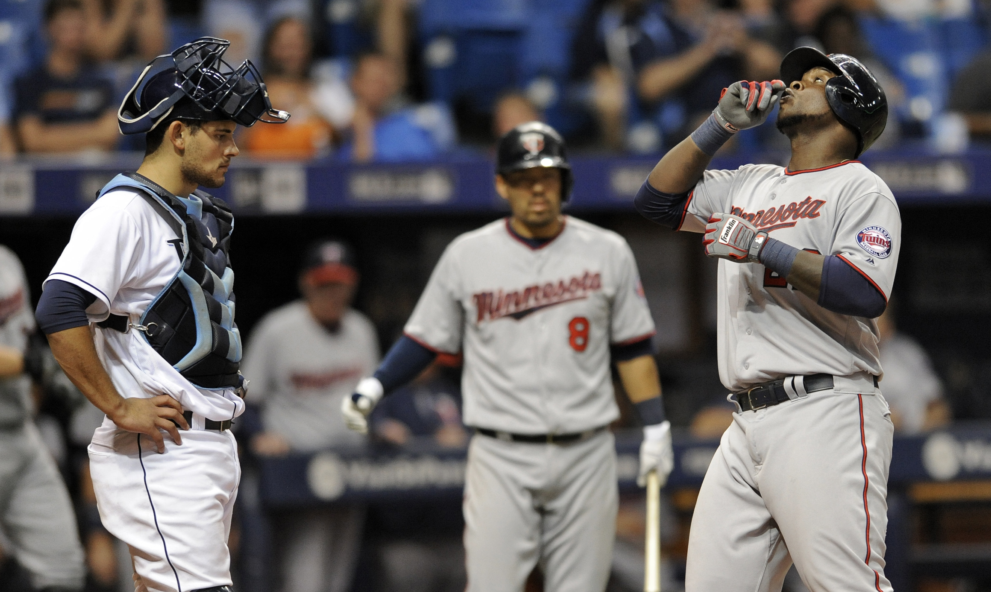 Minnesota Twins' Kurt Suzuki (8) and Tampa Bay Rays catcher Luke Maile, left, looks on as Minnesota's Miguel Sano, right, crosses home plate after hitting a solo home run off Tampa Bay reliever Erasmo Ramirez during the eighth inning of a baseball game Fr