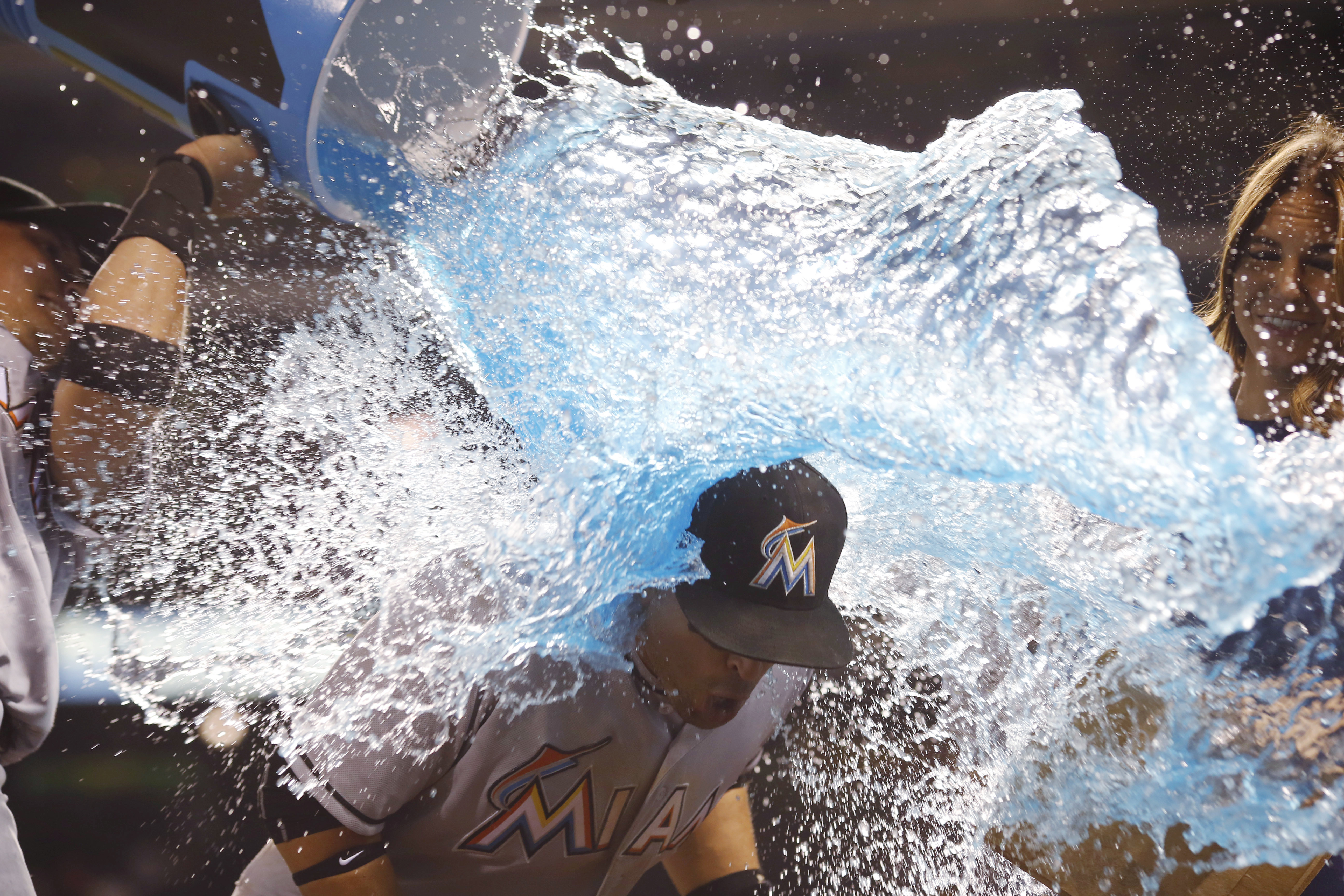 Miami Marlins second baseman Miguel Rojas, left, douses third baseman Martin Prado after the Marlins' 5-3 victory over the Colorado Rockies in a baseball game Friday, Aug. 5, 2016 in Denver. Prado hit a two-run single in the ninth inning. (AP Photo/David