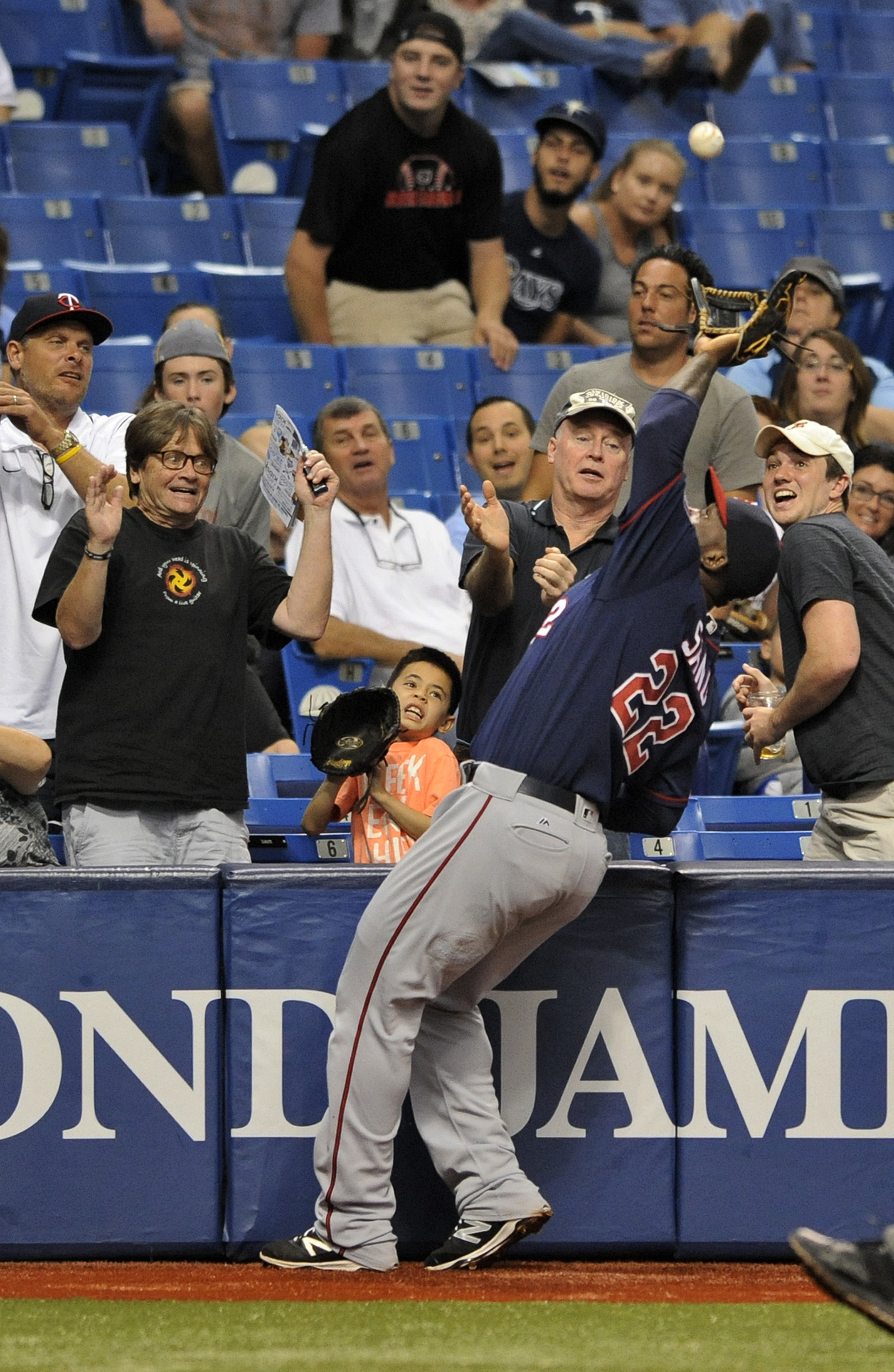 Fans watch as Minnesota Twins third baseman Miguel Sano reaches for a foul ball hit by Tampa Bay Rays' Corey Dickerson during the second inning of a baseball game Sunday, Aug. 7, 2016, in St. Petersburg, Fla. (AP Photo/Steve Nesius)