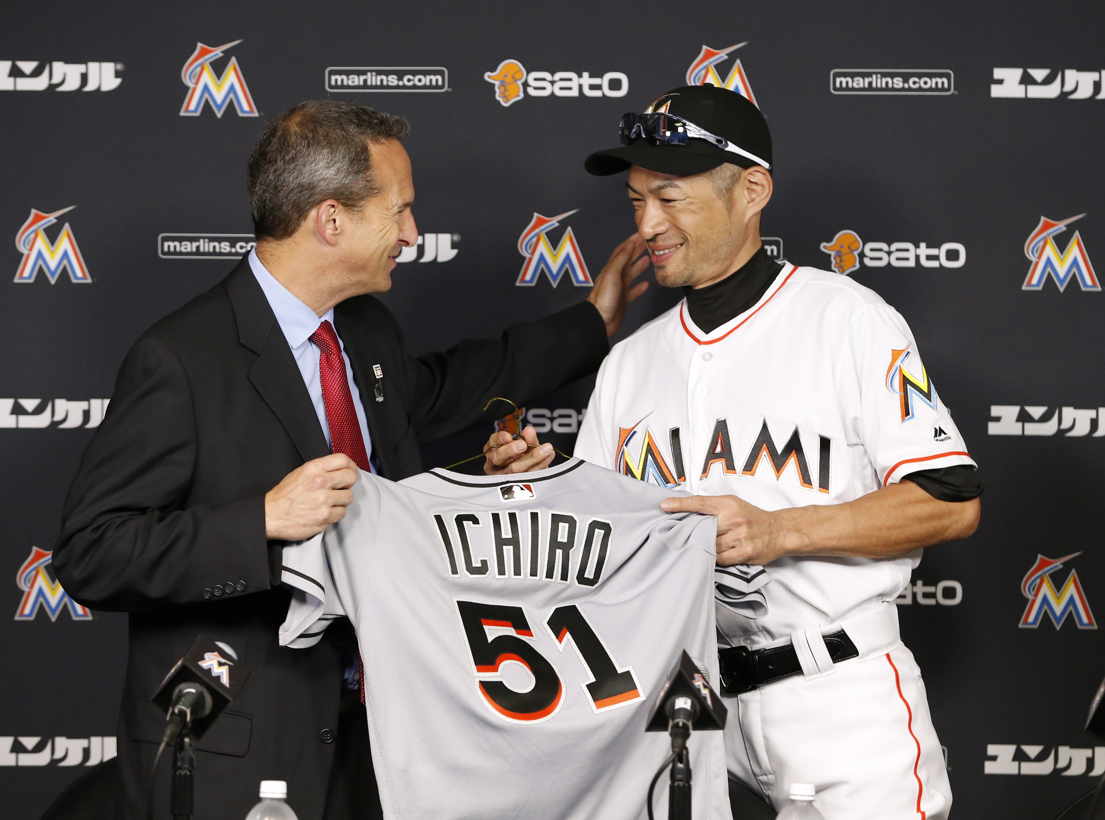Jeff Idelson, left, president of the National Baseball Hall of Fame and Museum, and Miami Marlins' Ichiro Suzuki smile as Suzuki gives Idelson items from his 3,000 major league hit during a news conference, Monday, Aug. 8, 2016, in Miami. (AP Photo/Wilfre