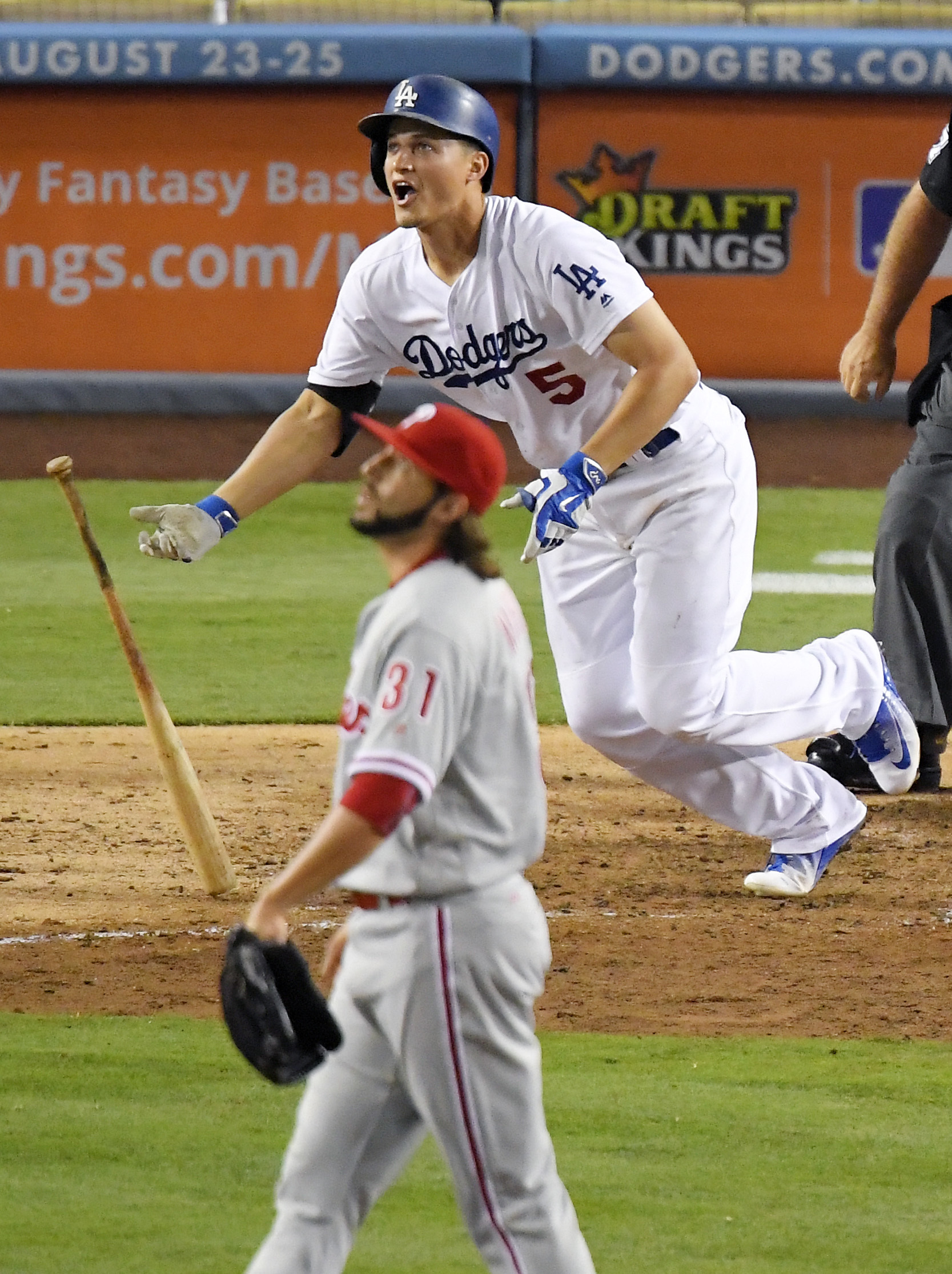 Los Angeles Dodgers' Corey Seager, top, hits a solo home run as Philadelphia Phillies relief pitcher Michael Mariot watches during the seventh inning of a baseball game, Monday, Aug. 8, 2016, in Los Angeles. (AP Photo/Mark J. Terrill)