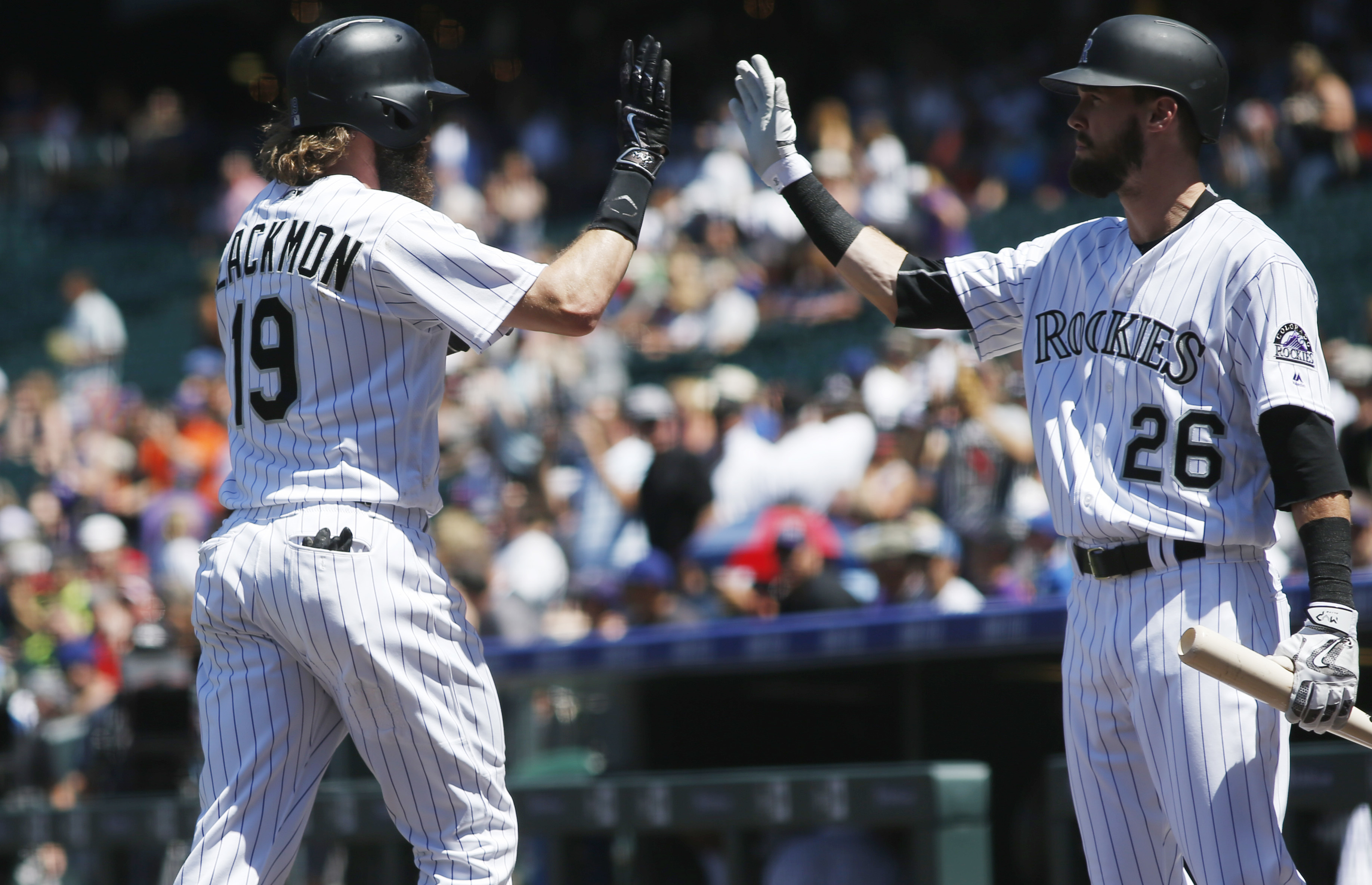 Colorado Rockies' Charlie Blackmon, left, is congratulated by David Dahl after hitting a solo home run off Texas Rangers starting pitcher A.J. Griffin in the first inning of a baseball game Tuesday, Aug. 9, 2016 in Denver. (AP Photo/David Zalubowski)