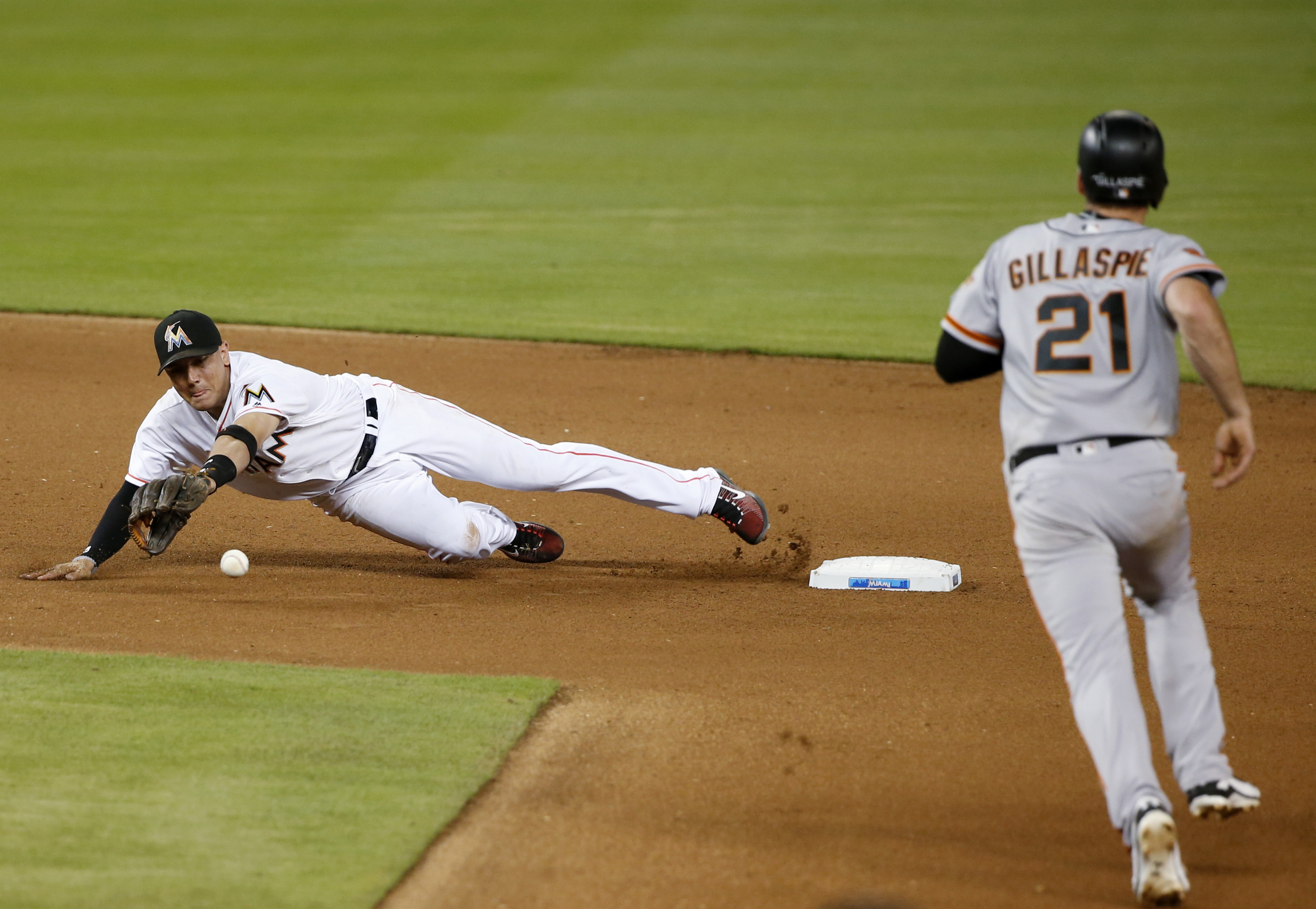 Miami Marlins shortstop Miguel Rojas dives for a throw from second baseman Dee Gordon, not seen, to put out San Francisco Giants' Conor Gillaspie (21) at second base during the fourth inning of a baseball game, Tuesday, Aug. 9, 2016, in Miami. (AP Photo/W