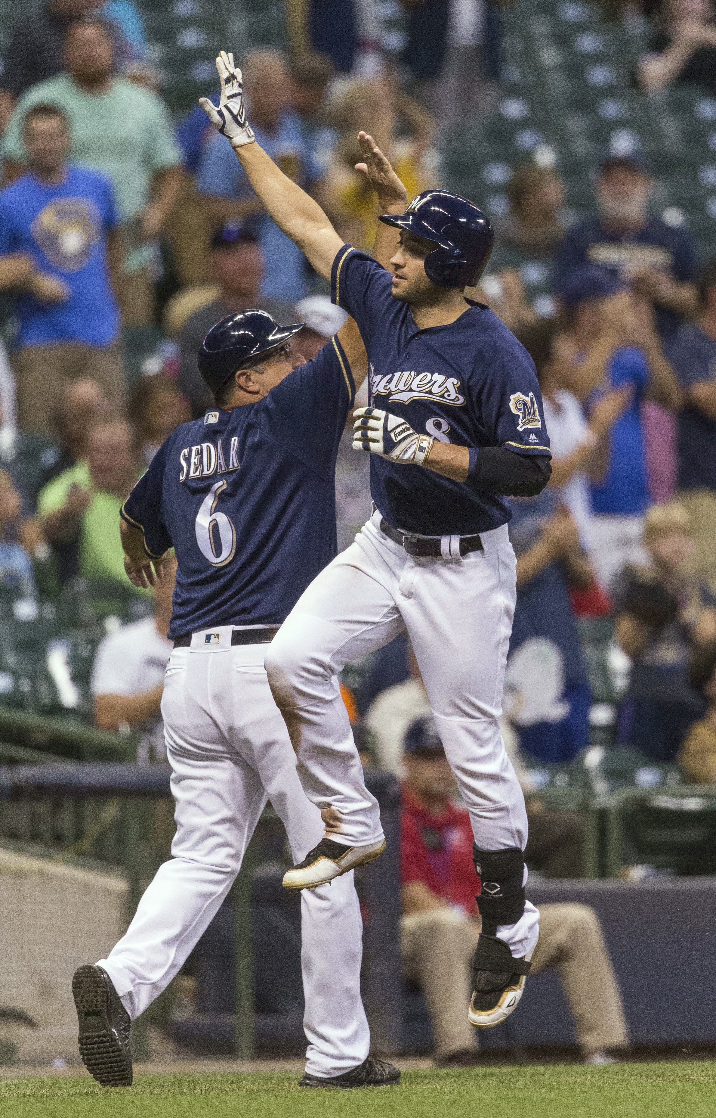 Milwaukee Brewers' Ryan Braun leaps for a high-five from third base coach Ed Sedar after hitting a solo home run off of Atlanta Braves' Tyrell Jenkins during the fourth inning of a baseball game Tuesday, Aug. 9, 2016, in Milwaukee. (AP Photo/Tom Lynn)