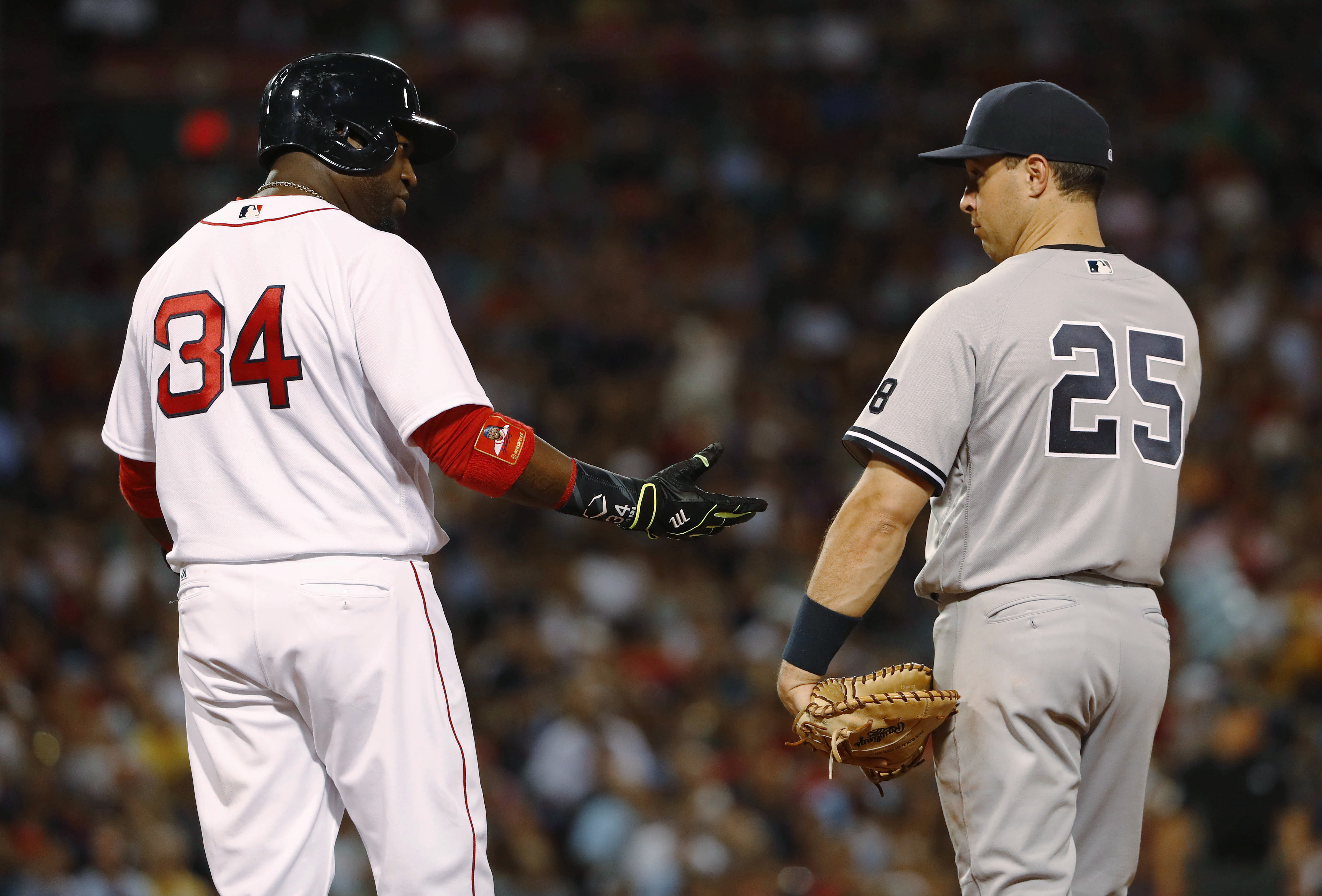 Boston Red Sox designated hitter David Ortiz (34) talks with New York Yankees first baseman Mark Teixeira after his RBI single during the fifth inning of a baseball game at Fenway Park in Boston on Tuesday, Aug. 9, 2016. (AP Photo/Winslow Townson)