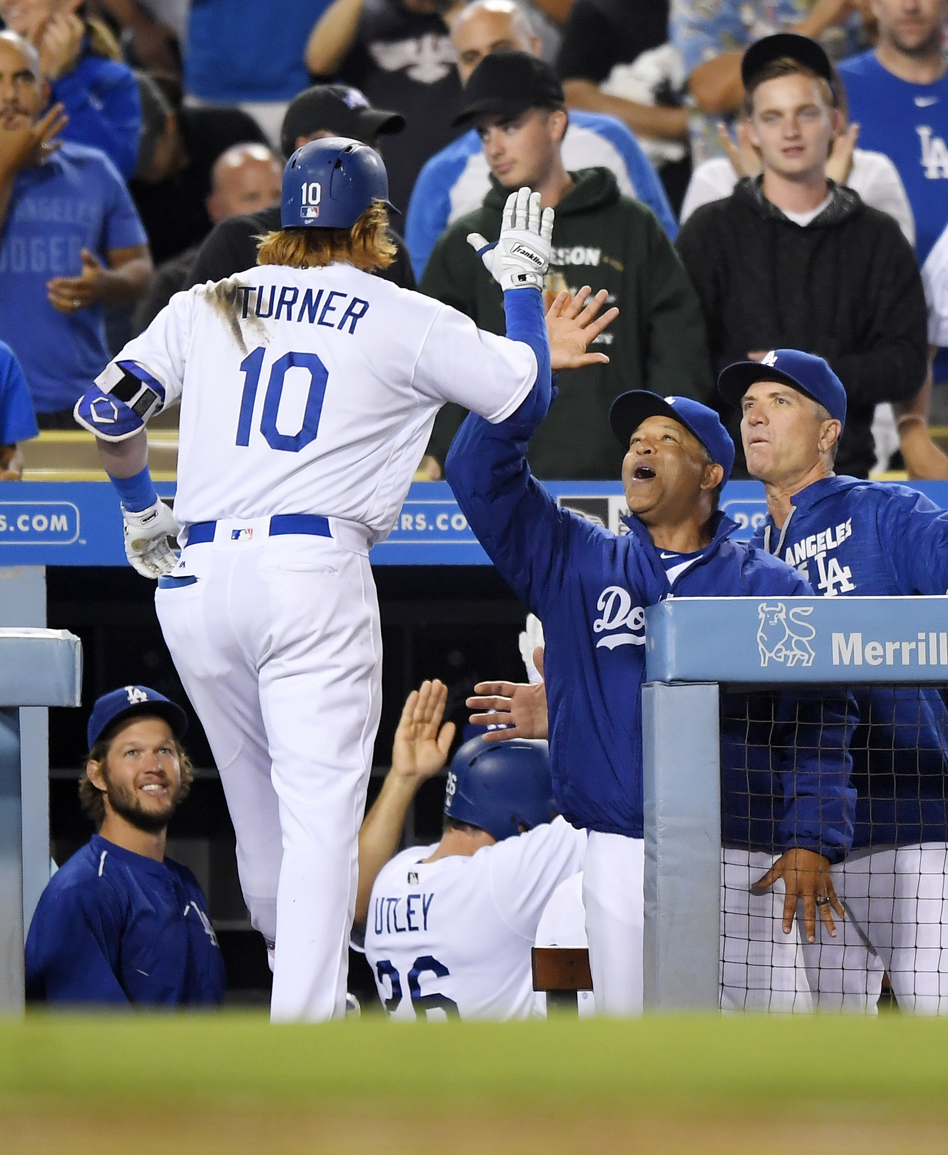 Los Angeles Dodgers' Justin Turner, left, is congratulated by manager Dave Roberts, second from right, and bench coach Bob Geren after hitting a two-run home run during the fourth inning of a baseball game against the Philadelphia PHillies, Tuesday, Aug.