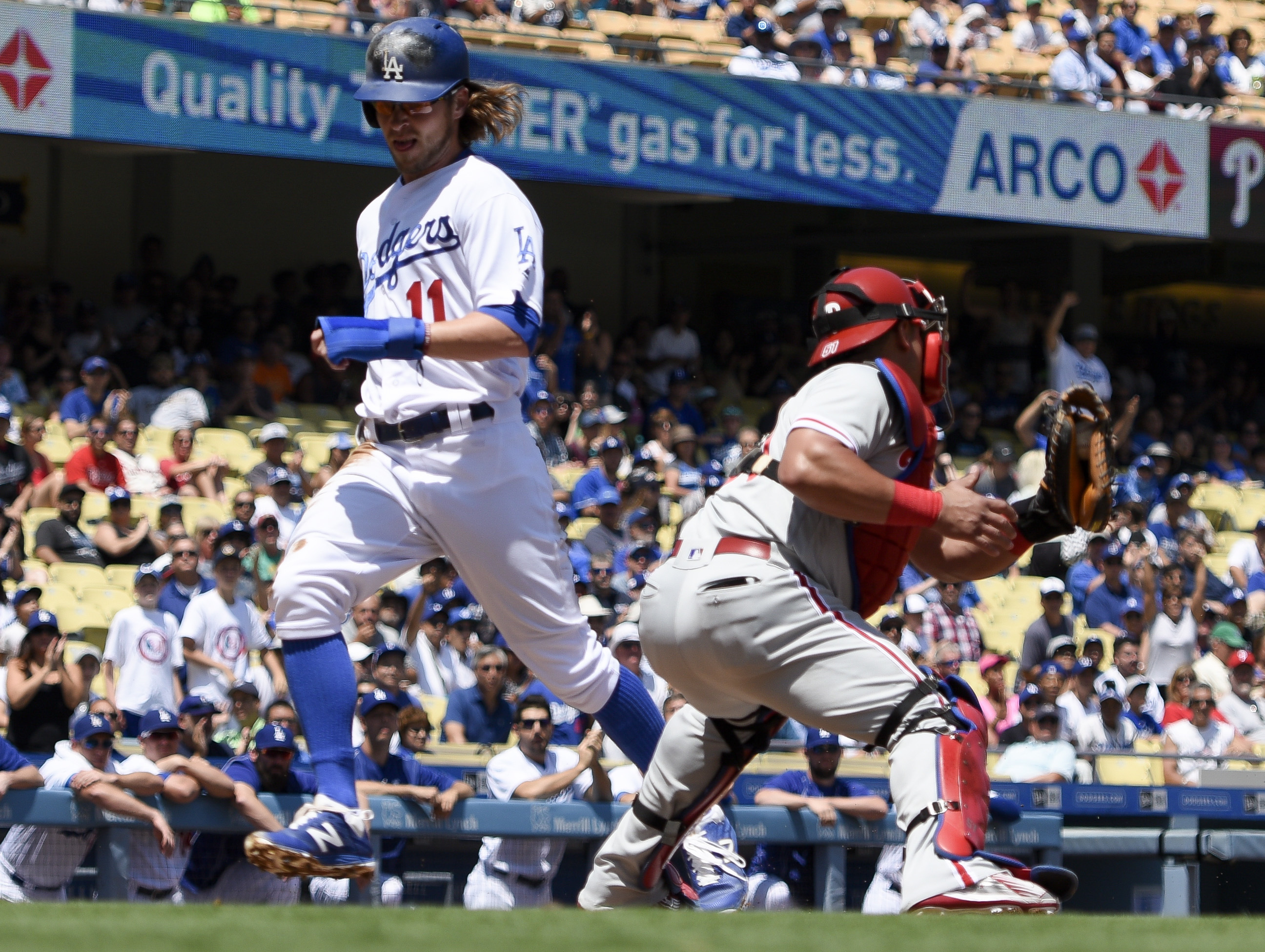 Los Angeles Dodgers' Josh Reddick, left, scores a run ahead of Philadelphia Phillies catcher Carlos Ruiz, right, off an RBI double by Adrian Gonzalez, during the first inning of a baseball game in Los Angeles, Wednesday, Aug. 10, 2016. (AP Photo/Kelvin Ku