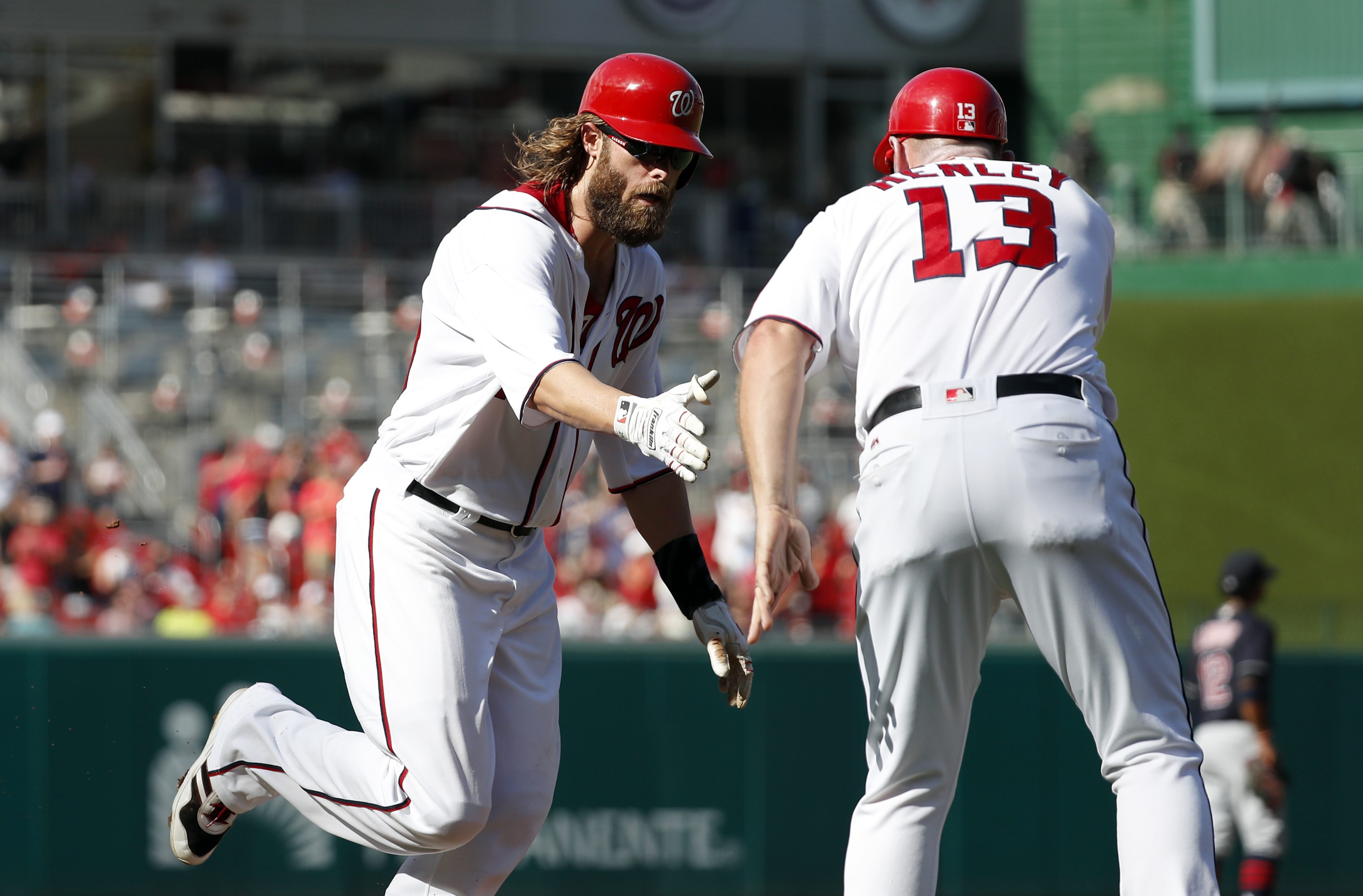Washington Nationals' Jayson Werth, left, is congratulated by third base coach Bob Henley (13) as he rounds the bases for his three-run homer during the second inning of a baseball game against the Cleveland Indians at Nationals Park, Wednesday, Aug. 10,