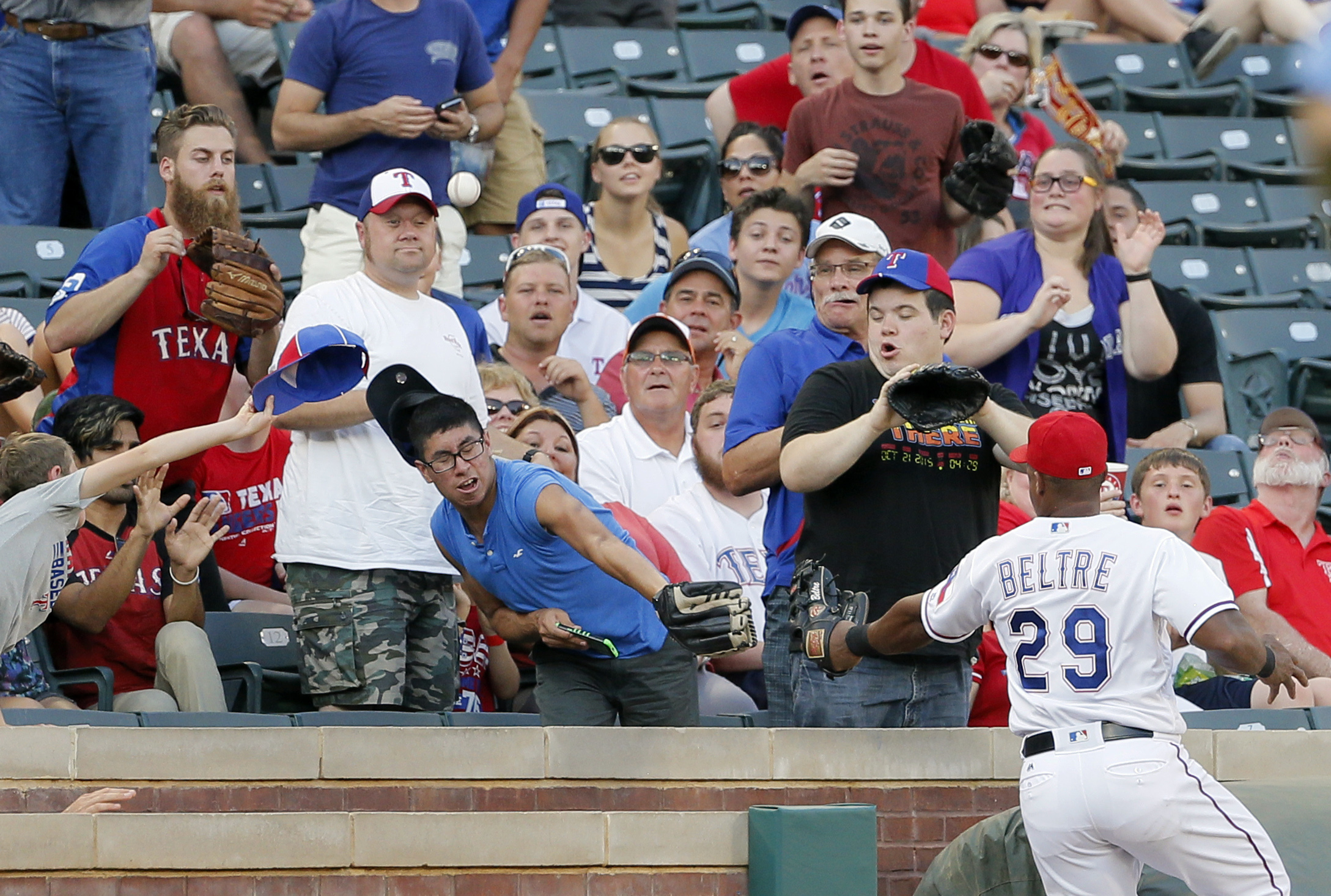 Fans and Texas Rangers third baseman Adrian Beltre (29) attempt to reach pop foul ball hit by Colorado Rockies' Mark Reynolds during the first inning of a baseball game Wednesday, Aug. 10, 2016, in Arlington, Texas. (AP Photo/Tony Gutierrez)