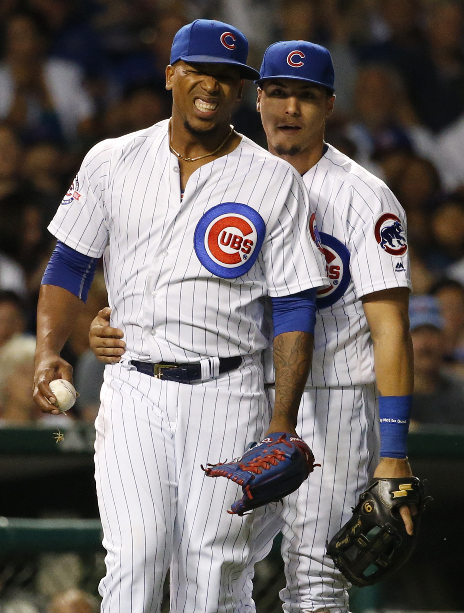 Chicago Cubs relief pitcher Pedro Strop, left, reacts after injury and third baseman Javier Baez stands behind him during the eighth inning of a baseball game against the Los Angeles Angels in Chicago, Wednesday, Aug. 10, 2016. Strop left the game. (AP Ph