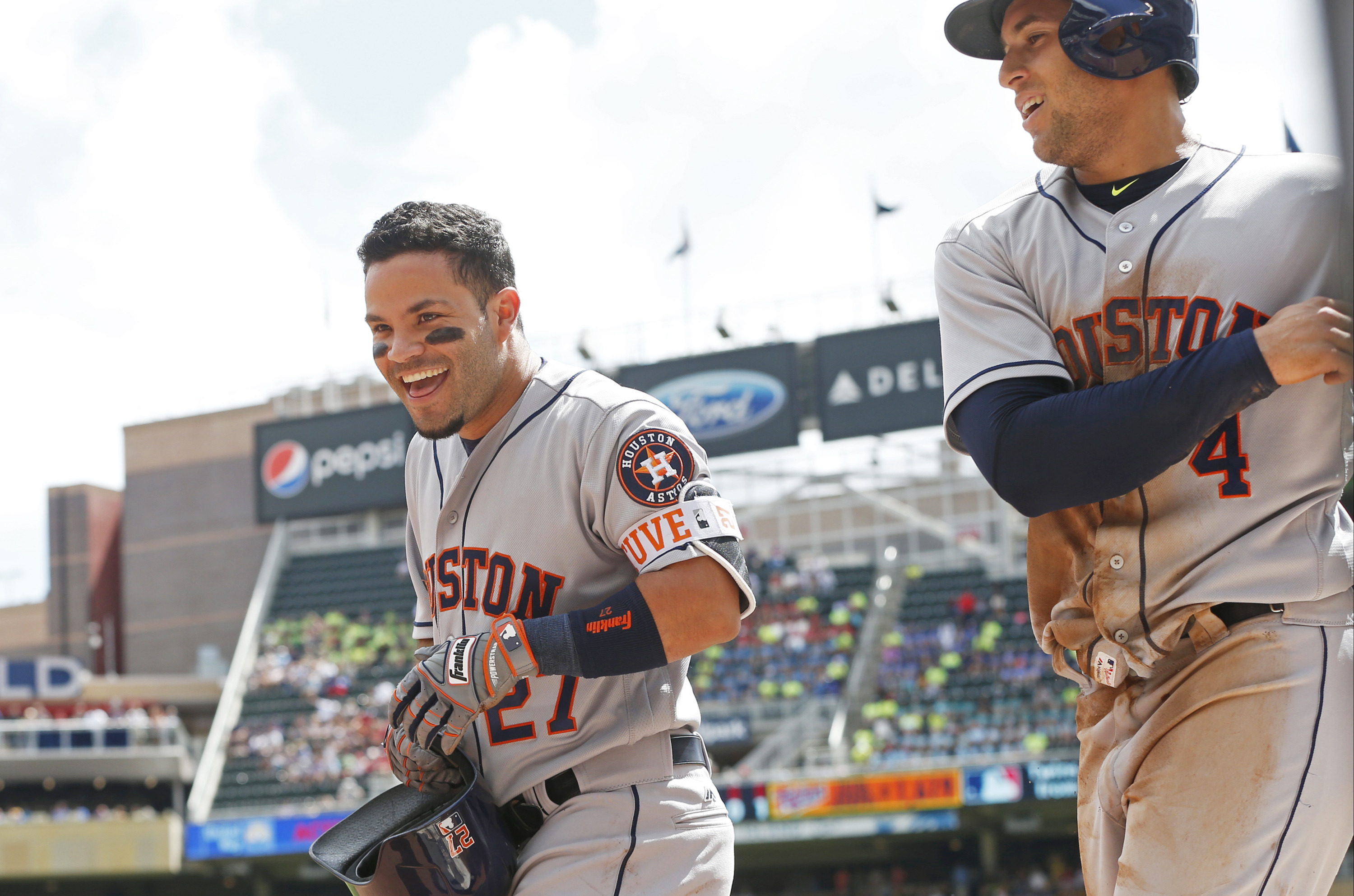 Houston Astros' Jose Altuve, left, and George Springer head to the dugout after scoring in the first inning of a baseball game against the Minnesota Twins Thursday, Aug. 11, 2016 in Minneapolis. (AP Photo/Jim Mone)