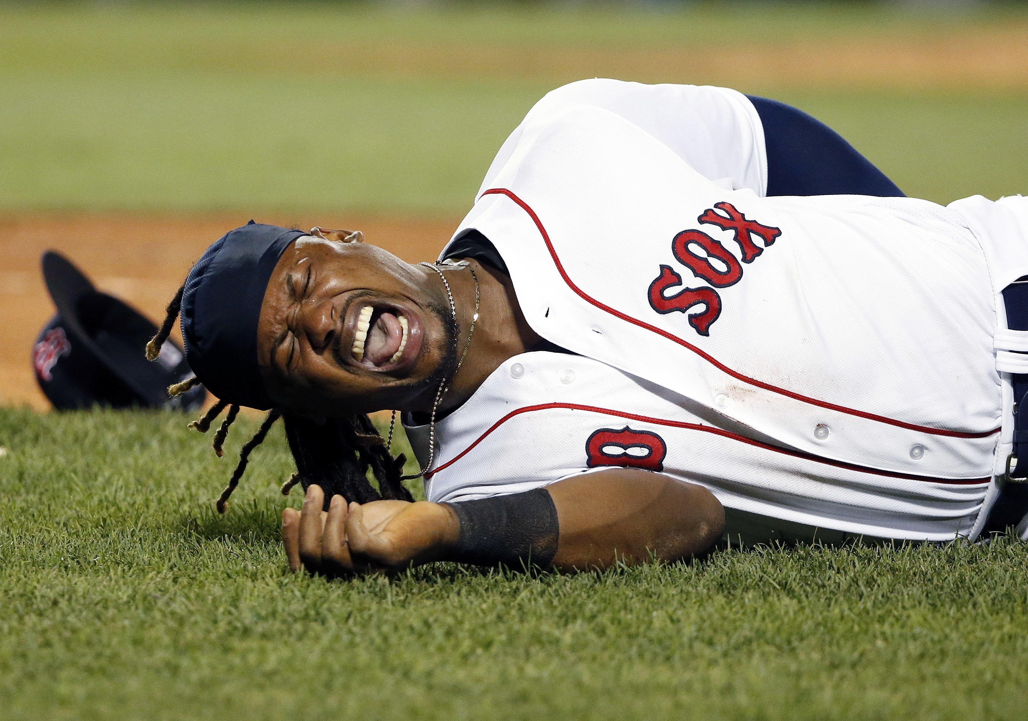 Boston Red Sox's Hanley Ramirez writhes on the ground after colliding with New York Yankees' Gary Sanchez as Sanchez ran out his single during the eighth inning of a baseball game in Boston, Thursday, Aug. 11, 2016. (AP Photo/Michael Dwyer)