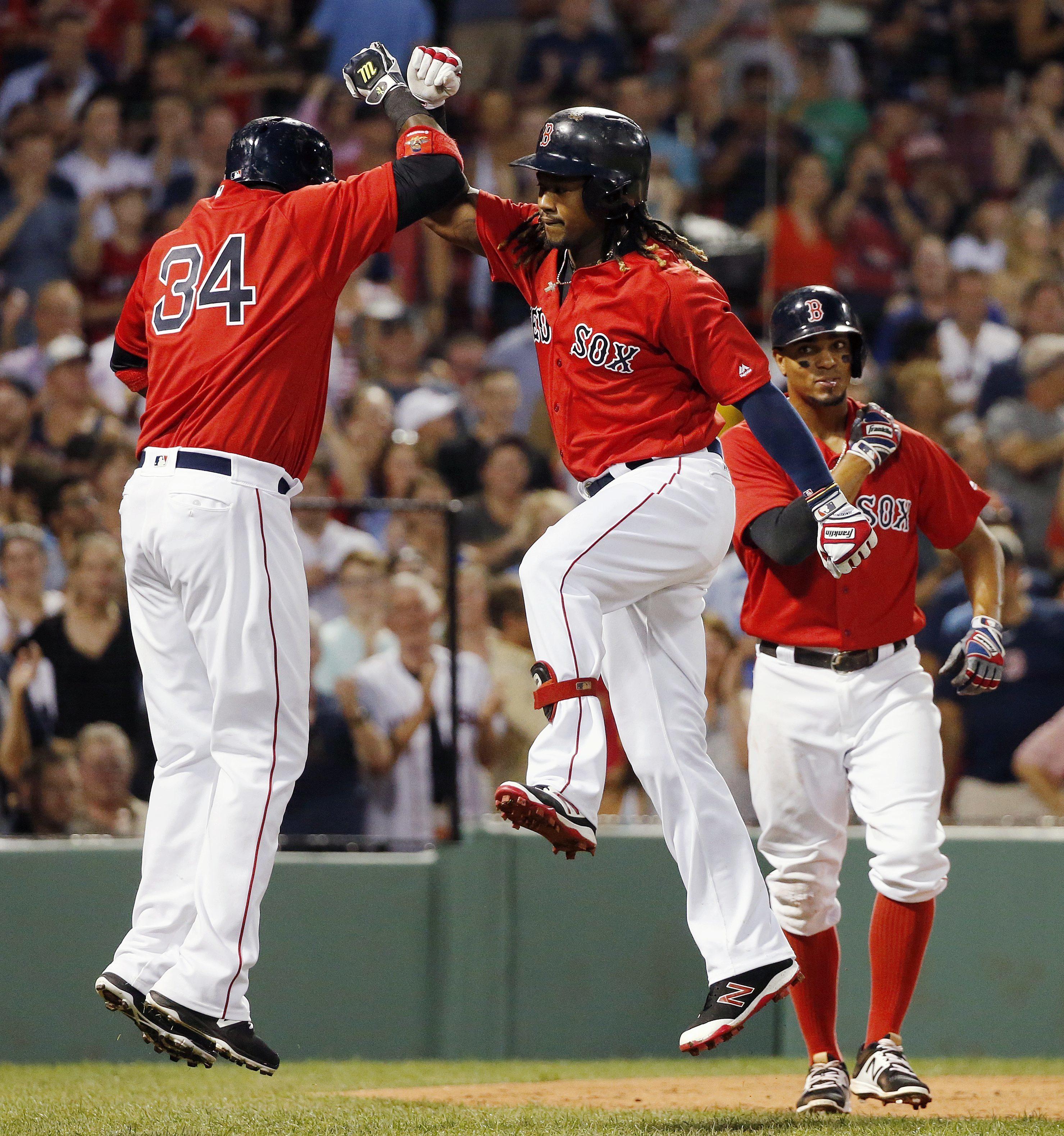 Boston Red Sox's Hanley Ramirez, center, celebrates his three-run home run that scored David Ortiz (34) and Xander Bogaerts, right, during the second inning of a baseball game against the Arizona Diamondbacks in Boston, Friday, Aug. 12, 2016. (AP Photo/Mi