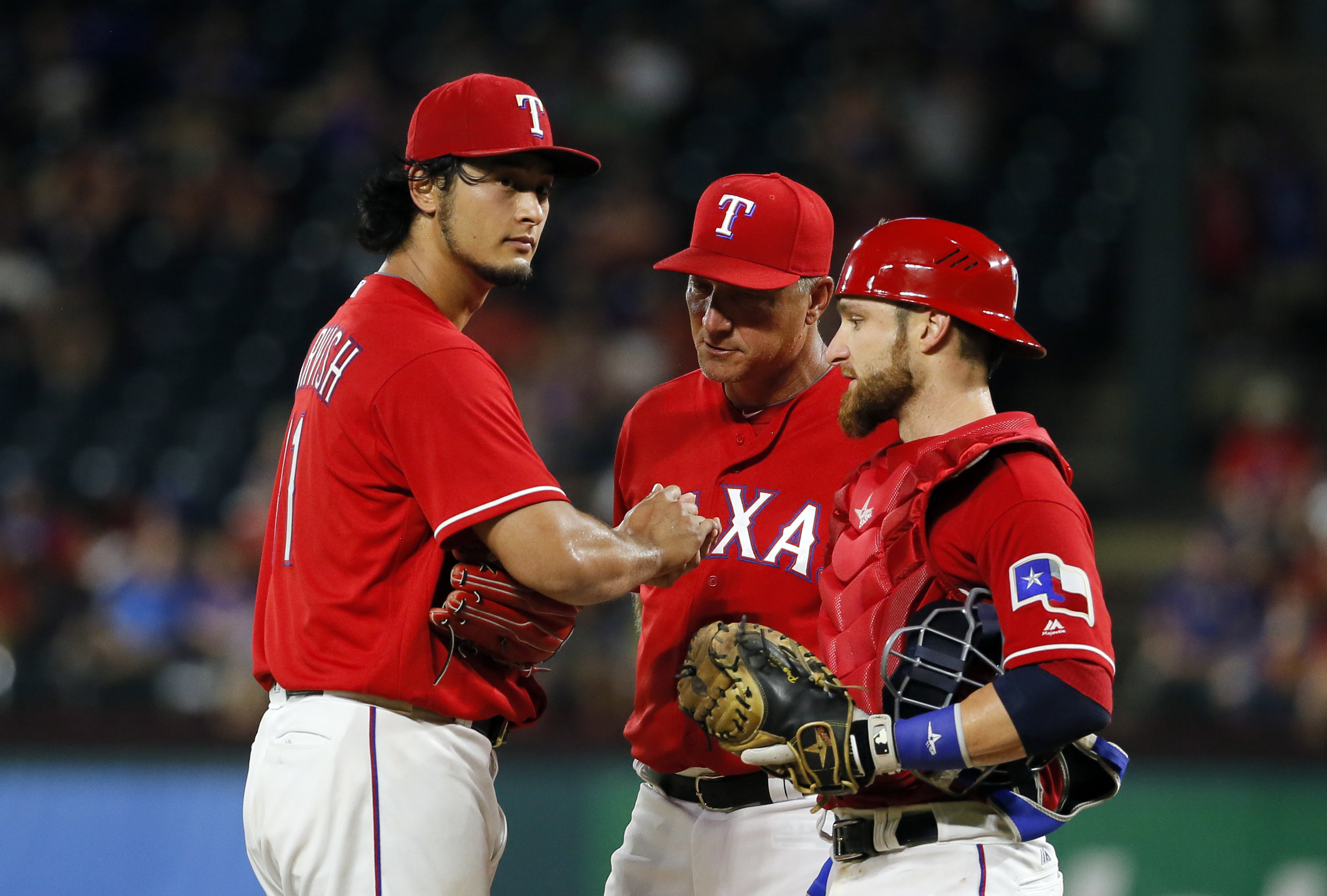 Texas Rangers' Yu Darvish, left, of Japan gets a visit from manager Jeff Banister, center, and teammate Jonathan Lucroy during the seventh inning of a baseball game against the Detroit Tigers early Saturday, Aug. 13, 2016, in Arlington, Texas. (AP Photo/T