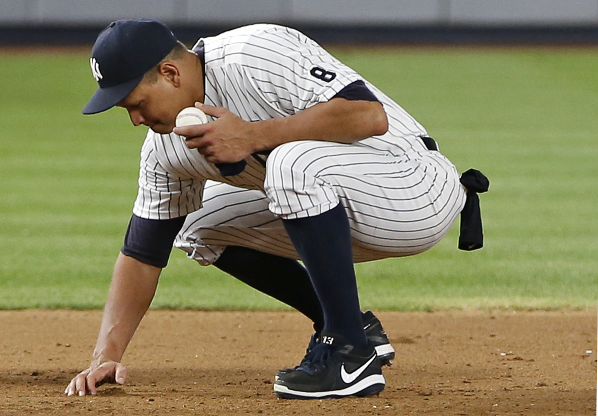 New York Yankees designated hitter Alex Rodriguez gathers dirt from the field near third base in his final game as a Yankee, at Yankee Stadium in New York, Friday, Aug. 12, 2016. He played part of the ninth inning at third base. The Yankees defeated the T